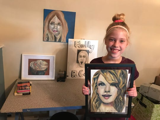 Molly Jablonowski, 12, holds a portrait of pop star Taylor Swift next to her drawing studio.