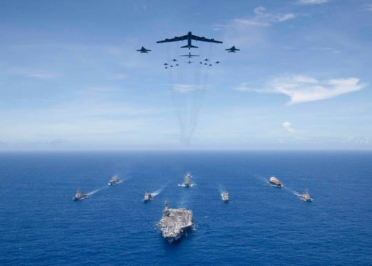 The USS Ronald Reagan leads a formation of Carrier Strike Group Five ships as U.S. Air Force B-52 Stratofortress aircraft and U.S. Navy F/A-18s pass overhead for a photo exercise during Valiant Shield 2018.