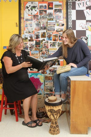 Esquire Hills elementary teacher Kim Witte, left, and Danielle Snyder look over photo albums of Witte's visits to a school in Malawi, a country in Africa.  Wittle, who has been volunteering at the school for years, visited Malawi this year with Snyder, a CK senior,  who was once an elementary school student of hers.