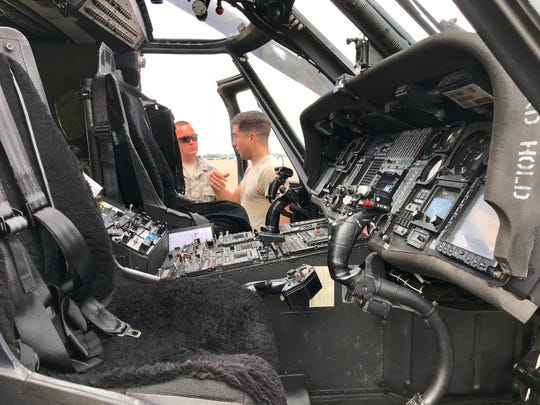 Senior Airman Phillip Dos Santos (right) chats with Senior Master Sgt. George Taylor outside the cockpit of an HH-60G Pave Hawk helicopter at Joint Base Charleston.