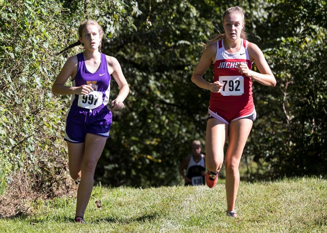 Unioto freshman Indy Spetnagel, left, looks at Jackson's Mazie Wechter as she runs alongside Wechter during the 2018 Aaron Reed Cross Country Invitational. Spetnagel finished second with a time of 22:18.76, with the Unioto girls team placing first overall with an average time of 25:24.42.