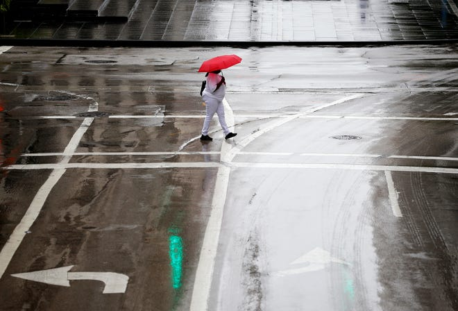 A woman crosses Fifth Street as rain falls Monday morning, September 17, 2018. Sunny skies are expected to return Tuesday but  a chance of rain is possible this weekend.