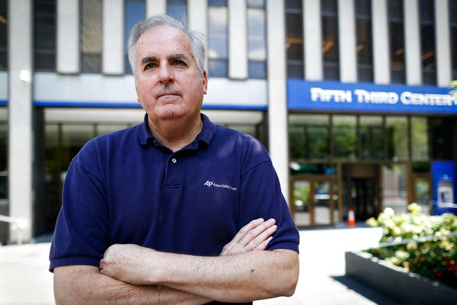 """In this Friday, Sept. 14, 2018 photo, Associated Press senior correspondent Dan Sewell poses for a photograph outside the scene of a shooting that occurred the previous week at Fountain Square, in Cincinnati. """"Over four decades with The Associated Press, I have many times thrown clothes into a bag, withdrawn a wad of cash, and stuffed my laptop with notebooks and pens before rushing by car or plane to a terrible event in someone else's hometown, state or country,"""" said Sewell. """"This time, it was in my town."""" (AP Photo/John Minchillo)"""