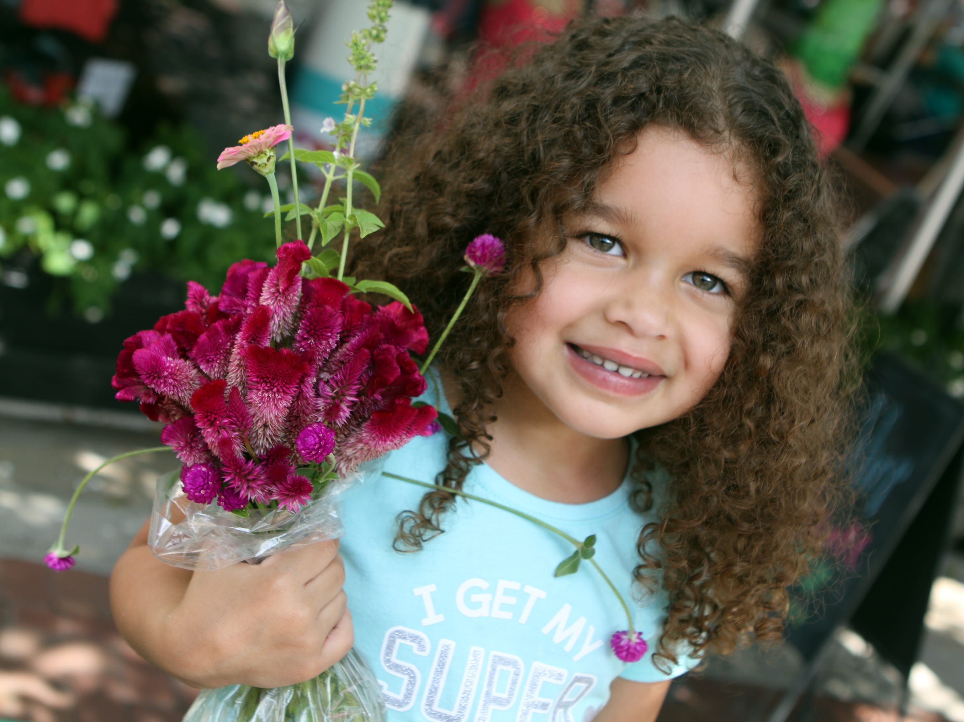 Phoenix Butler shows off her new flowers at Frolic on Franklin Saturday, Sept, 15, 2018.