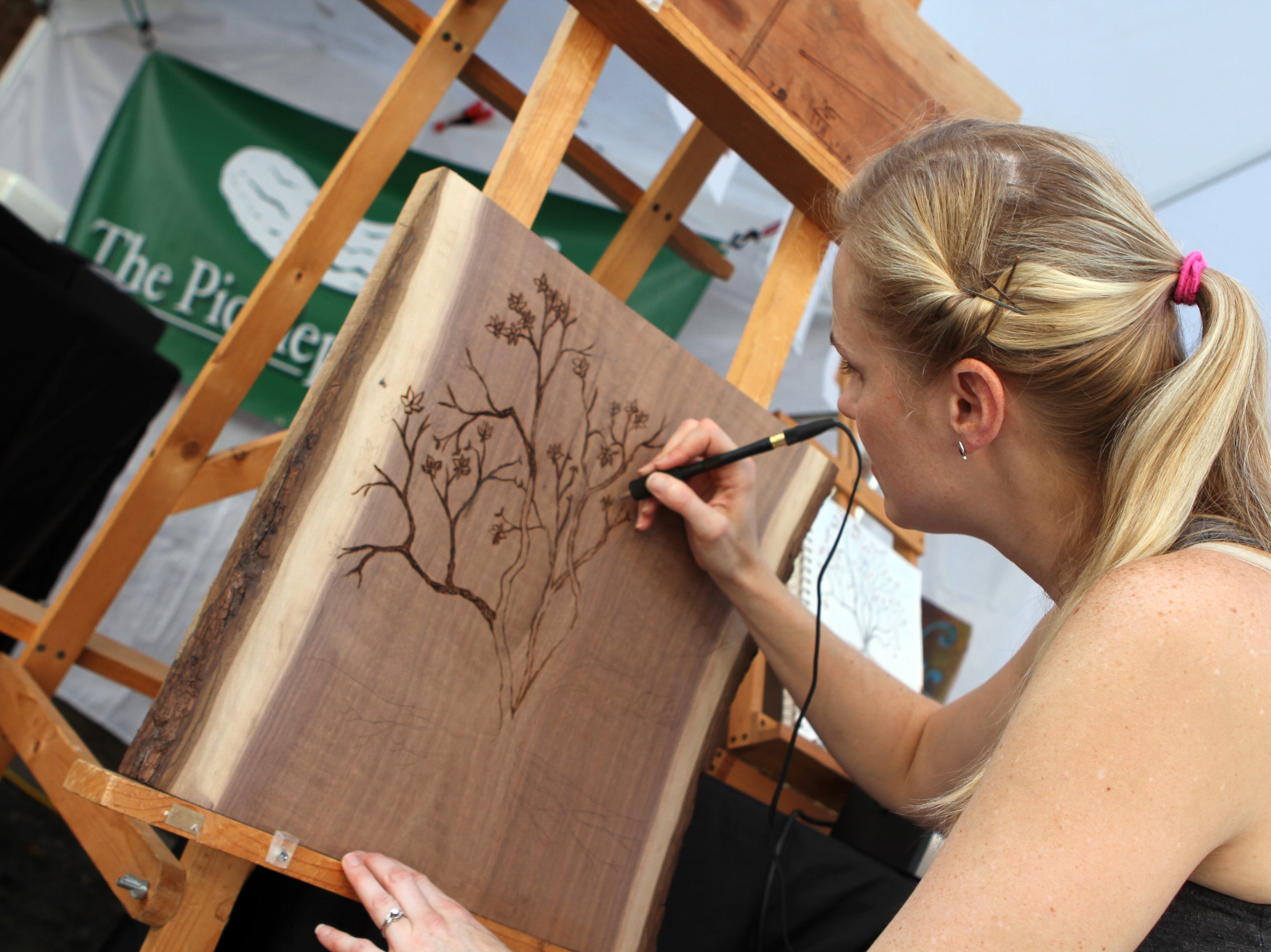 Jackie Lewis demonstrates the art of woodburning at Frolic on Franklin Saturday, Sept, 15, 2018.