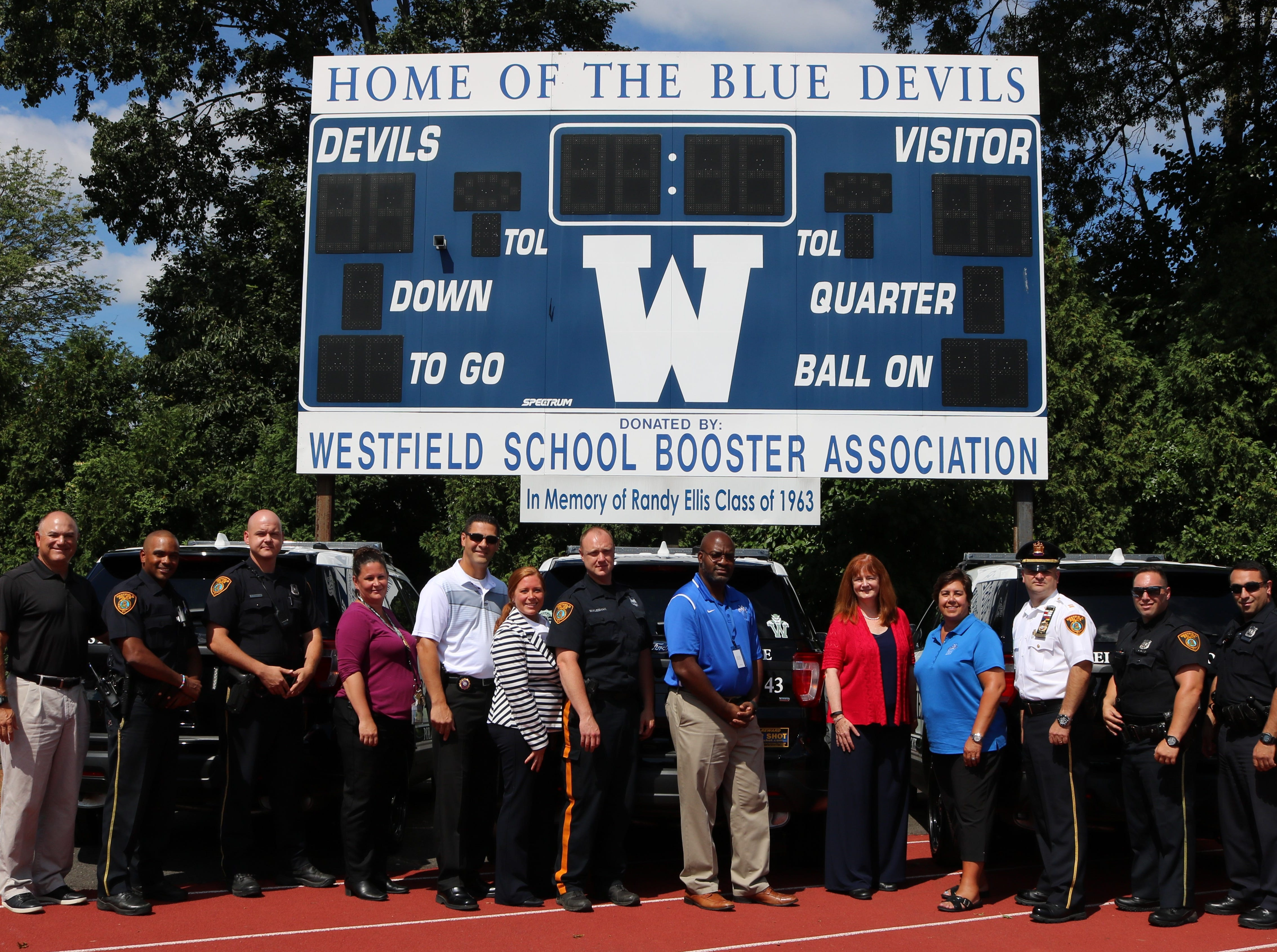 Westfield Police and school officials join together to display Blue Devil decals on more than 20 police vehicles, in support of student-athletes.  From left are:  Westfield High School Asst. Principal James DeSarno, School Resource Officer Ricardo Johnson, Officer Timothy Donovan, Detective Sergeant Nicole Stivale, Detective Lieutenant Jason Carter, WHS School Resource Officer Elizabeth Savnik, Officer William Kleeman, WHS Principal Derrick Nelson, Superintendent Dr. Margaret Dolan, WHS Athletic Director Sandra Mamary, Acting Chief of Police Christopher Battiloro, Officer Fortunato Riga and Officer Joseph Habeiche.