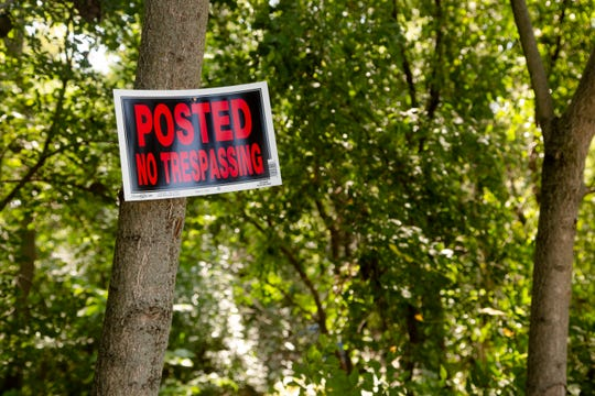 A no trespassing sign leads to a homeless camp in the woods behind the Des Moines OnStage building at 2124 Grand Ave. Sept. 11, 2018.