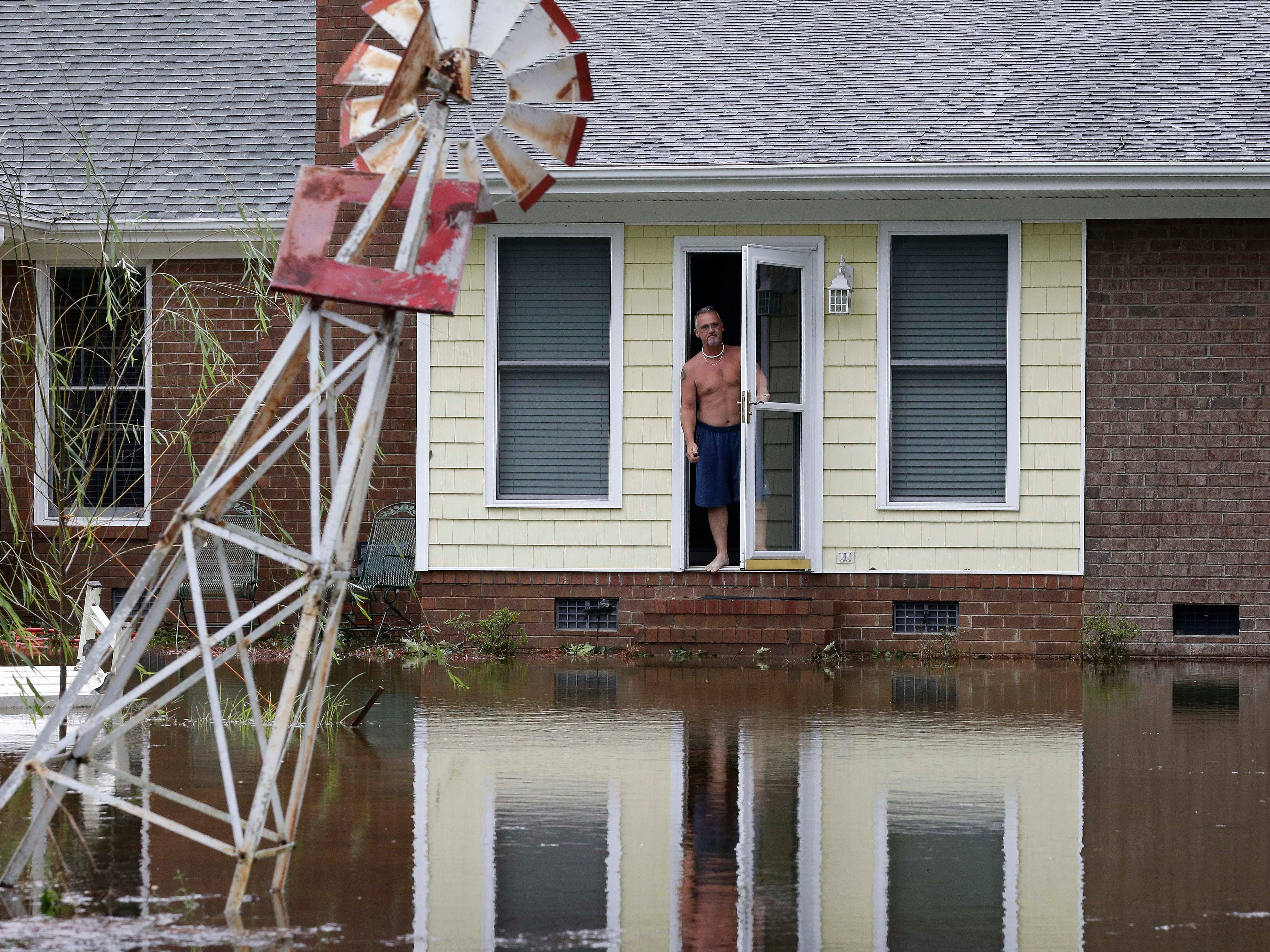 A man peers from his flooded home in Lumberton, N.C., Sunday, Sept. 16, 2018, in the aftermath of Hurricane Florence.