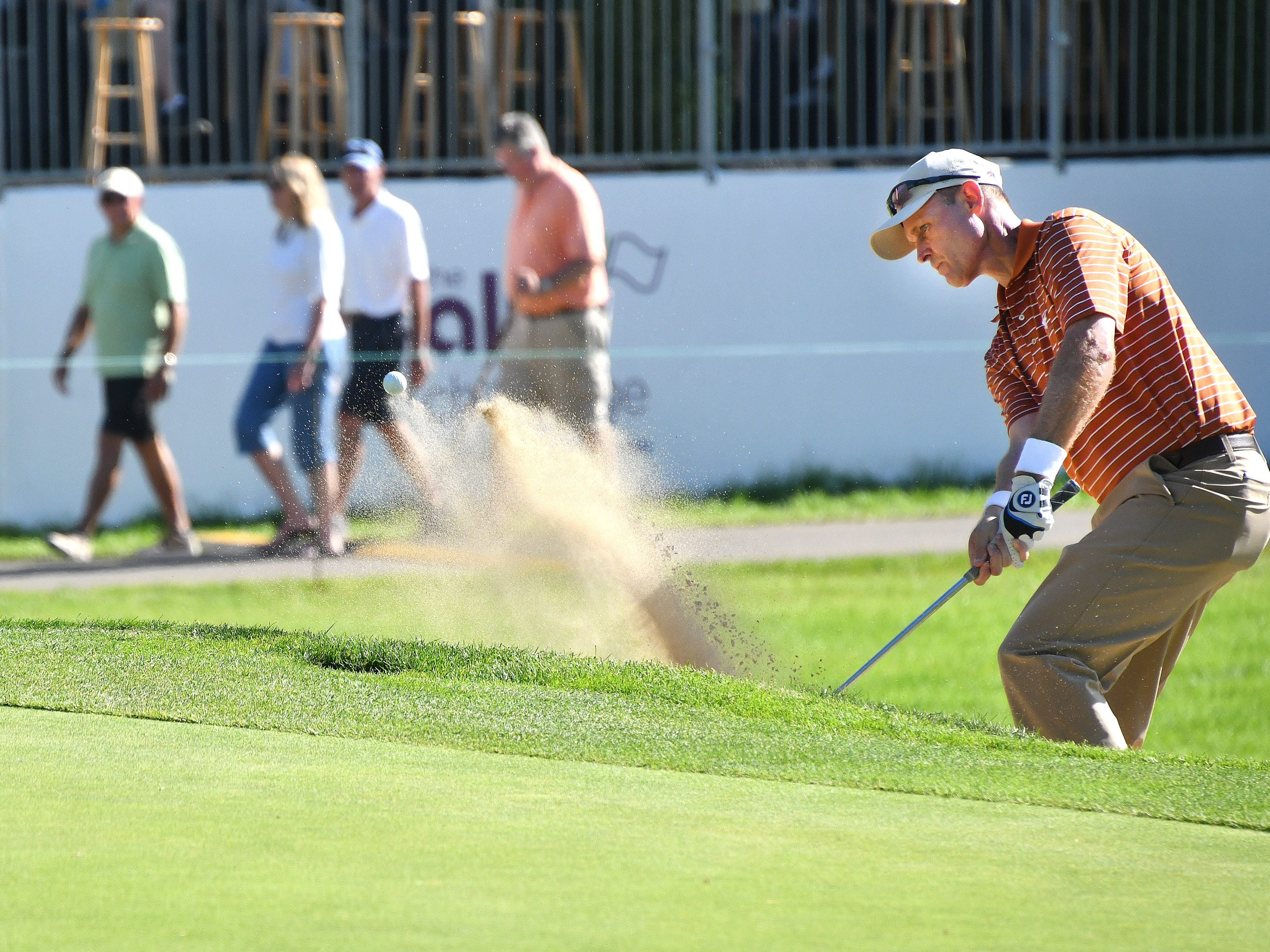 Bob Estes hits a shot out of the bunker in front of the 17th green.