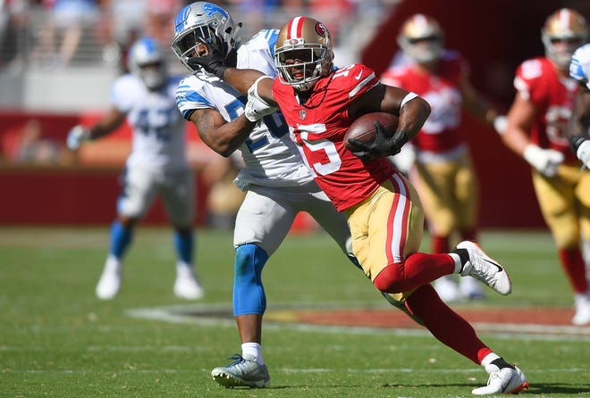 The 49ers' Pierre Garcon fights off the tackle of the Lions' Quandre Diggs during the fourth quarter.