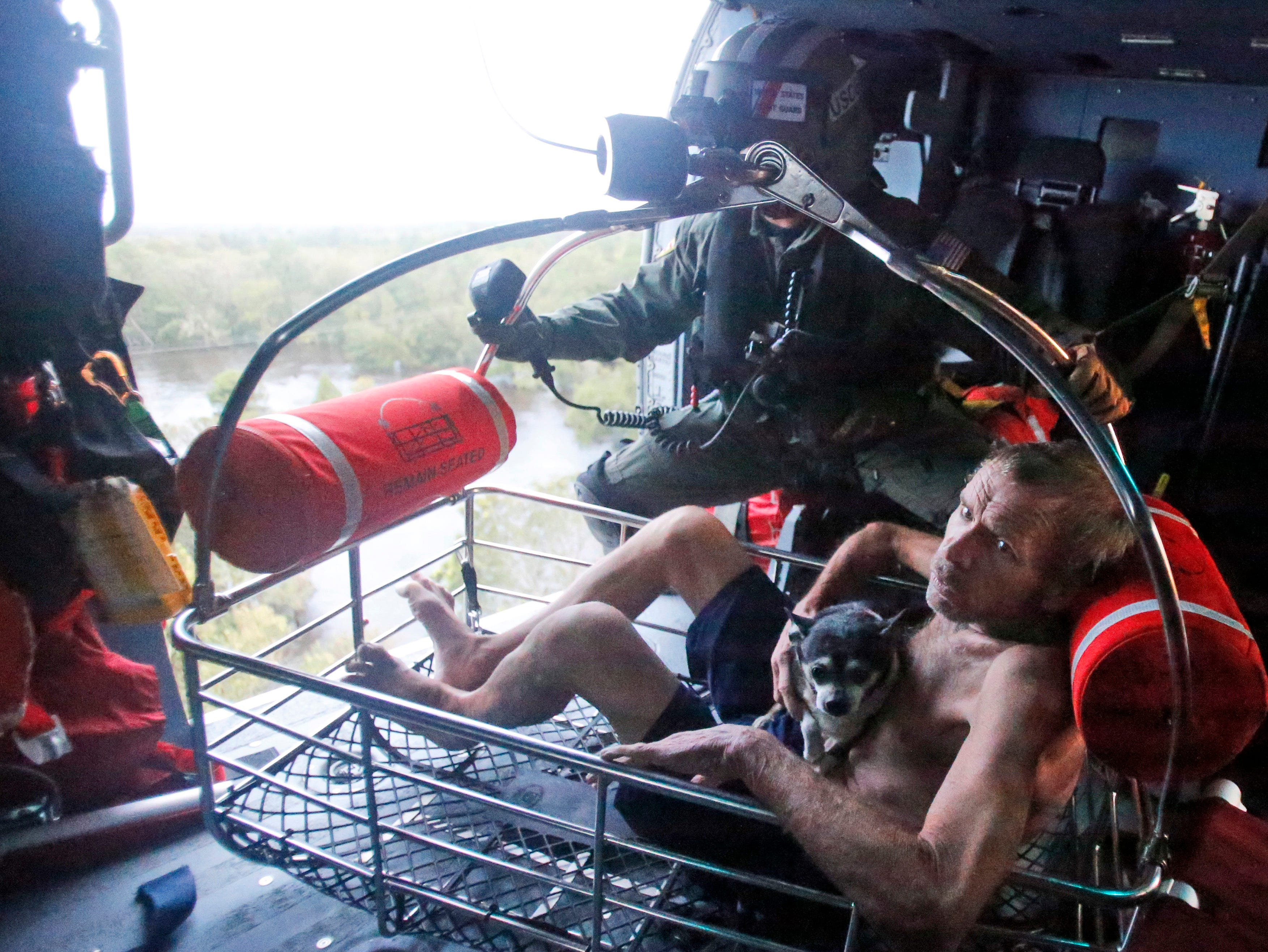 Willie Schubert of Pollocksville, N.C., is hoisted aboard a U.S. Coast Guard helicopter as he is rescued off a stranded van in Pollocksville on Monday, Sept. 17, 2018.