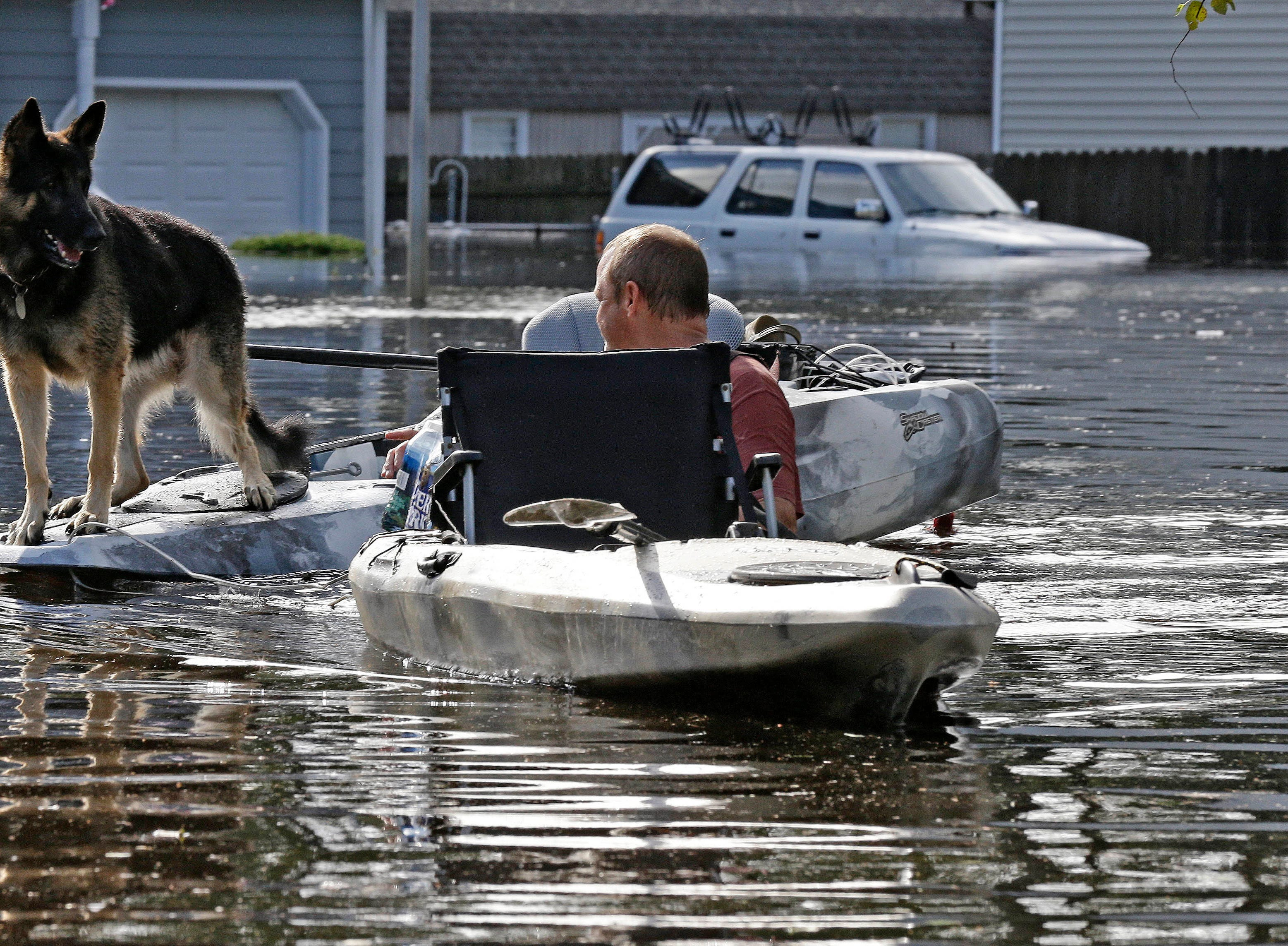 A man tries to get his dog out of a flooded neighborhood in Lumberton, N.C., Monday, Sept. 17, 2018, in the aftermath of Hurricane Florence.