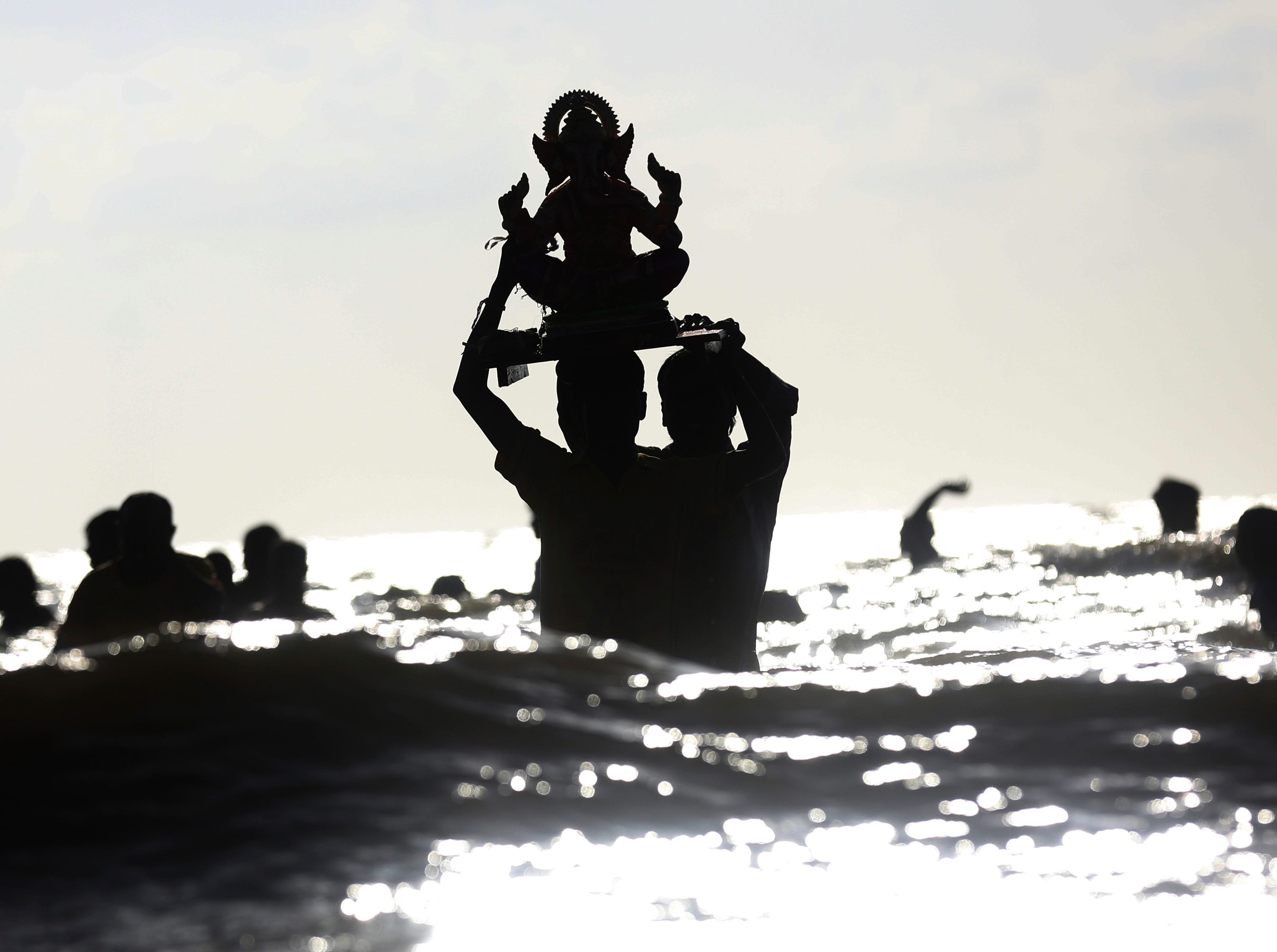 Devotees carry a Hindu god Ganesha idol into the Arabian sea for immersion on the fifth day of ten days long Ganesha festival in Mumbai, India, Monday, Sept. 17, 2018.