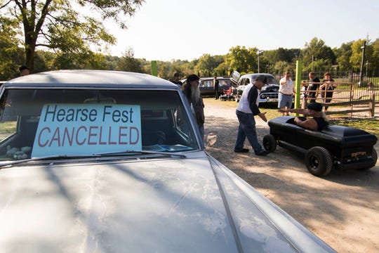 Volunteer Andy Mosier shakes hands with Dave Owens of Warren, pulling into the canceled Hearse Fest in Hell, Mich.