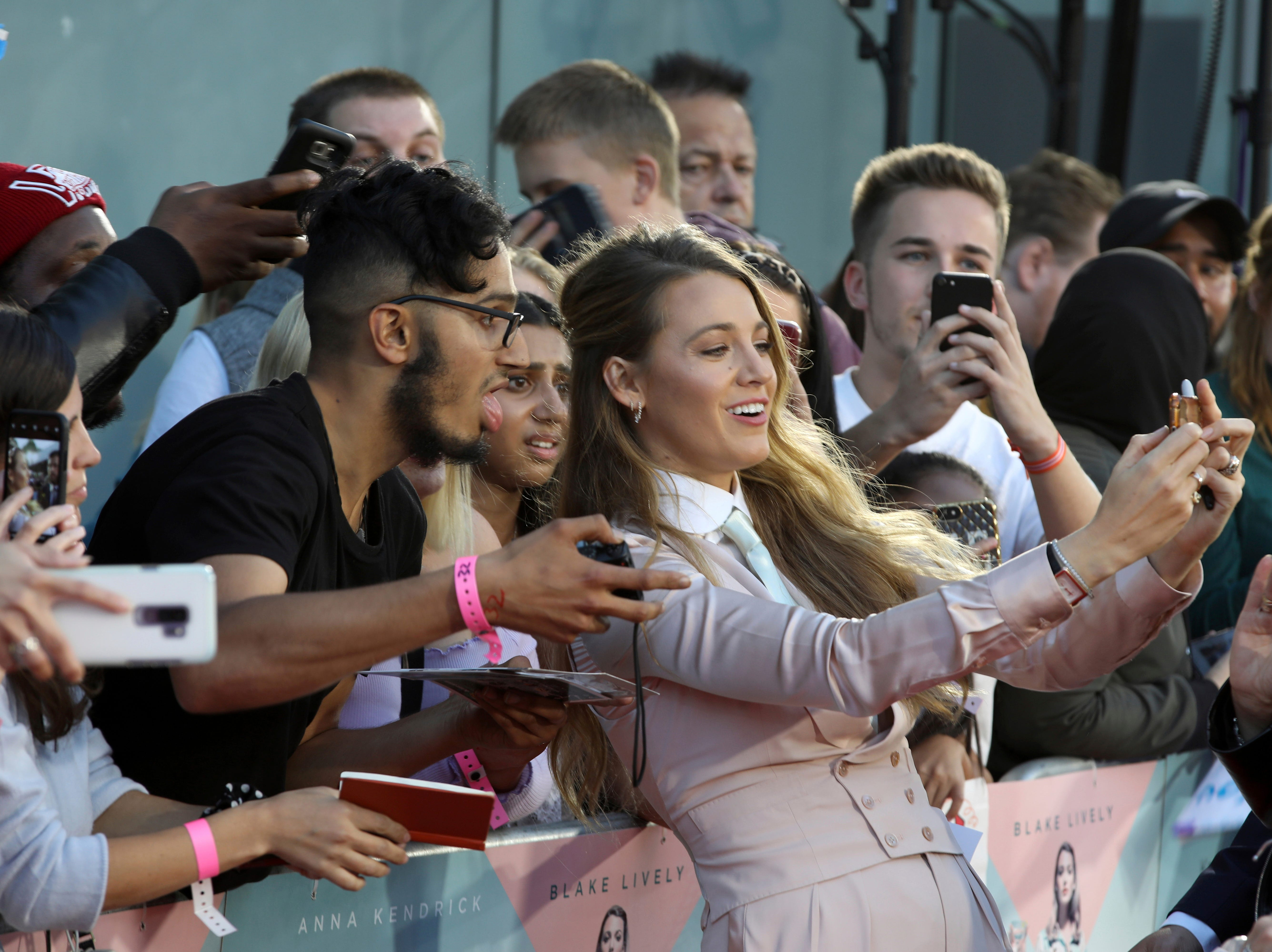 Actress Blake Lively poses with fans upon arrival at the premiere of the film 'A Simple Favour' in London, Monday, Sept. 17, 2018.