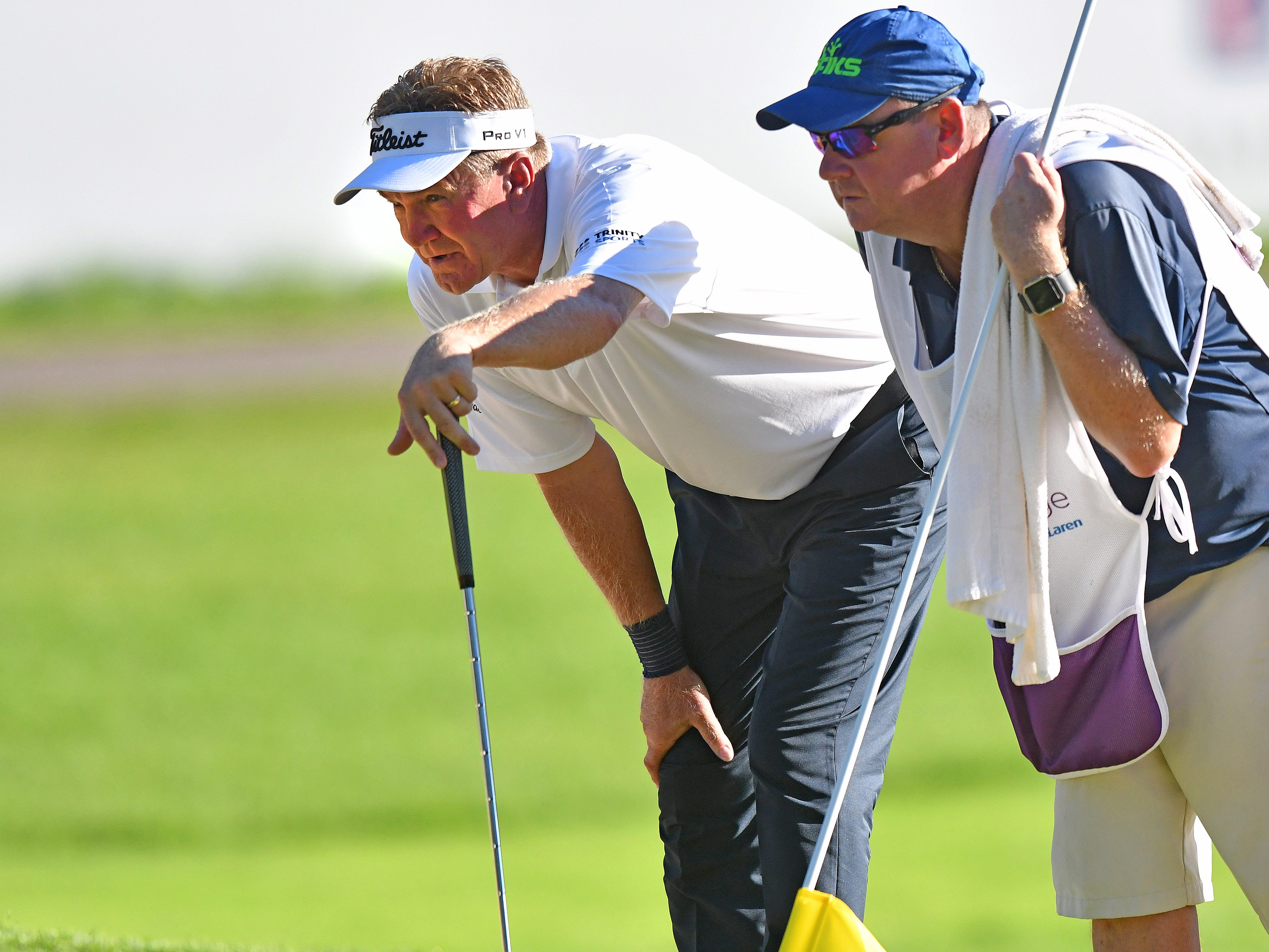 Paul Broadhurst and his caddy look over his putt on the 17th hole.