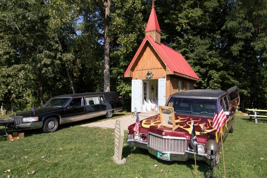 Several hearses flank the chapel where members of hearse collector clubs will convene for a wedding in Hell, Mich.