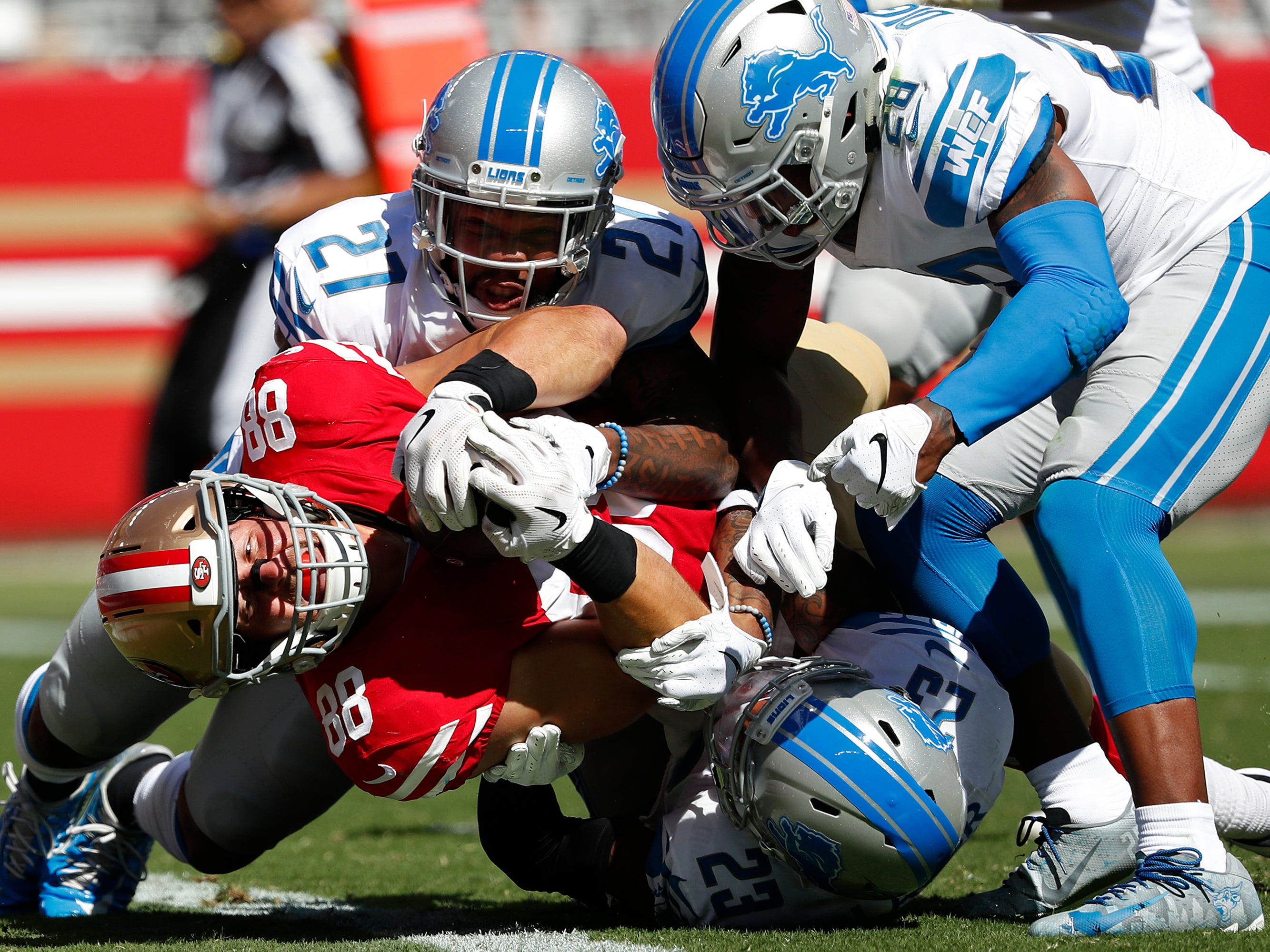 San Francisco 49ers tight end Garrett Celek (88) gets past Detroit Lions defensive back Glover Quin (27), cornerback Quandre Diggs (28) and defensive back Darius Slay (23) to score a touchdown during the second half.