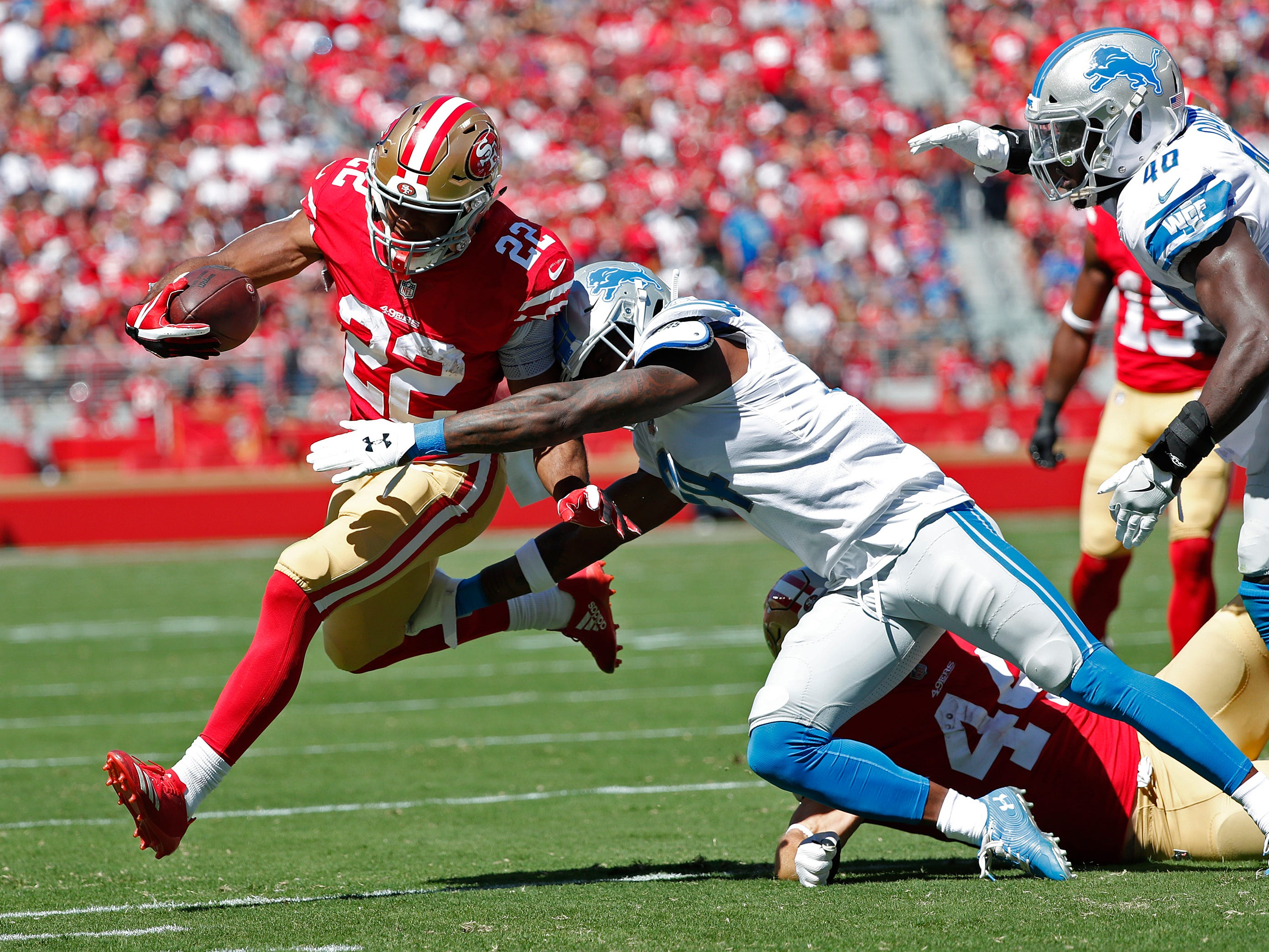 San Francisco 49ers running back Matt Breida (22) runs with the ball as Detroit Lions defensive back Nevin Lawson tries to stop him during the first half.