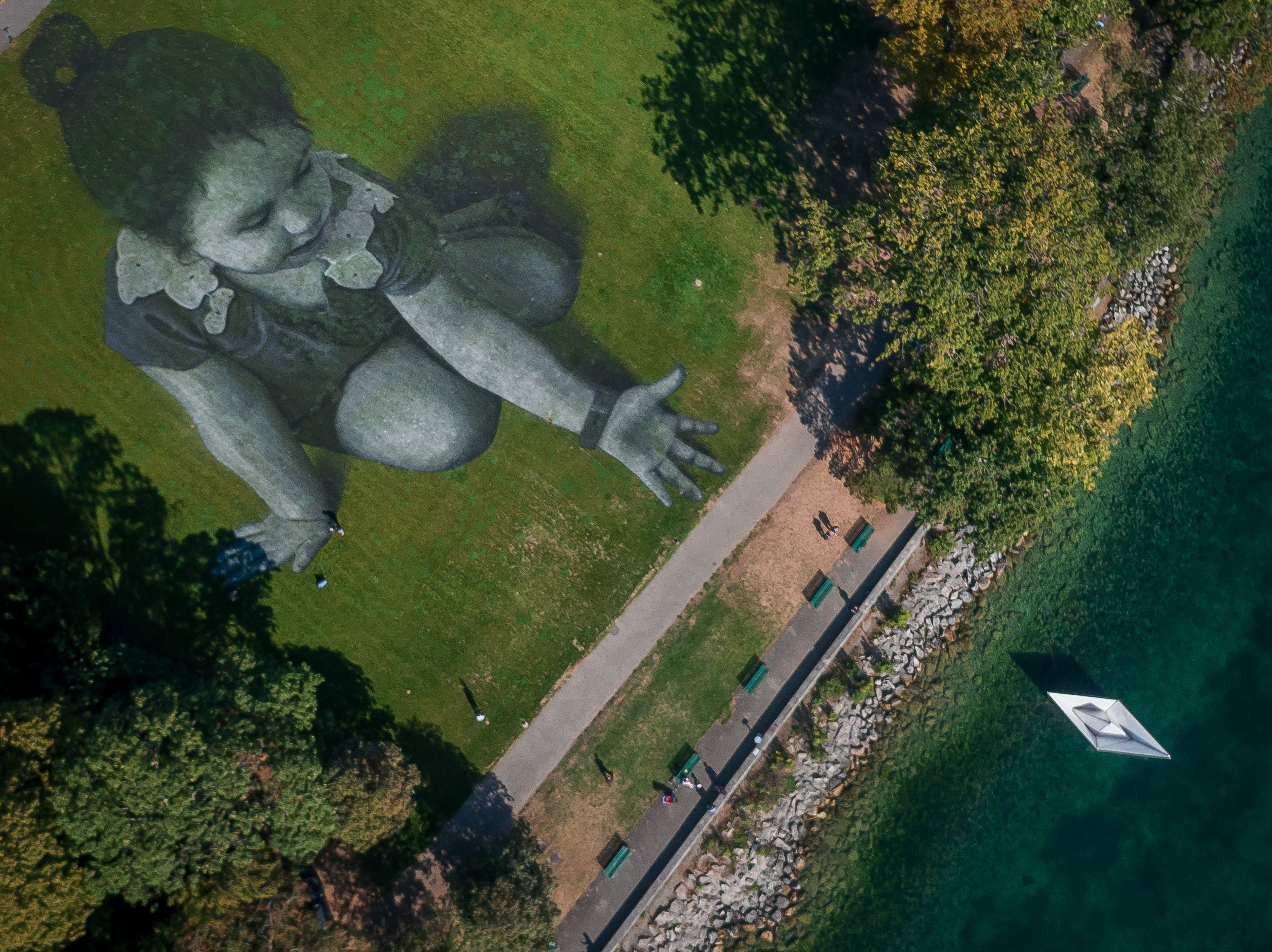 This aerial view shows French artist Saype's giant land art fresco representing a little girl droping an origami boat into Lake Geneva that he painted to support the cause of the NGO SOS Mediterranee, specializes in the rescue of migrants at sea on September 17, 2018 in Geneva.