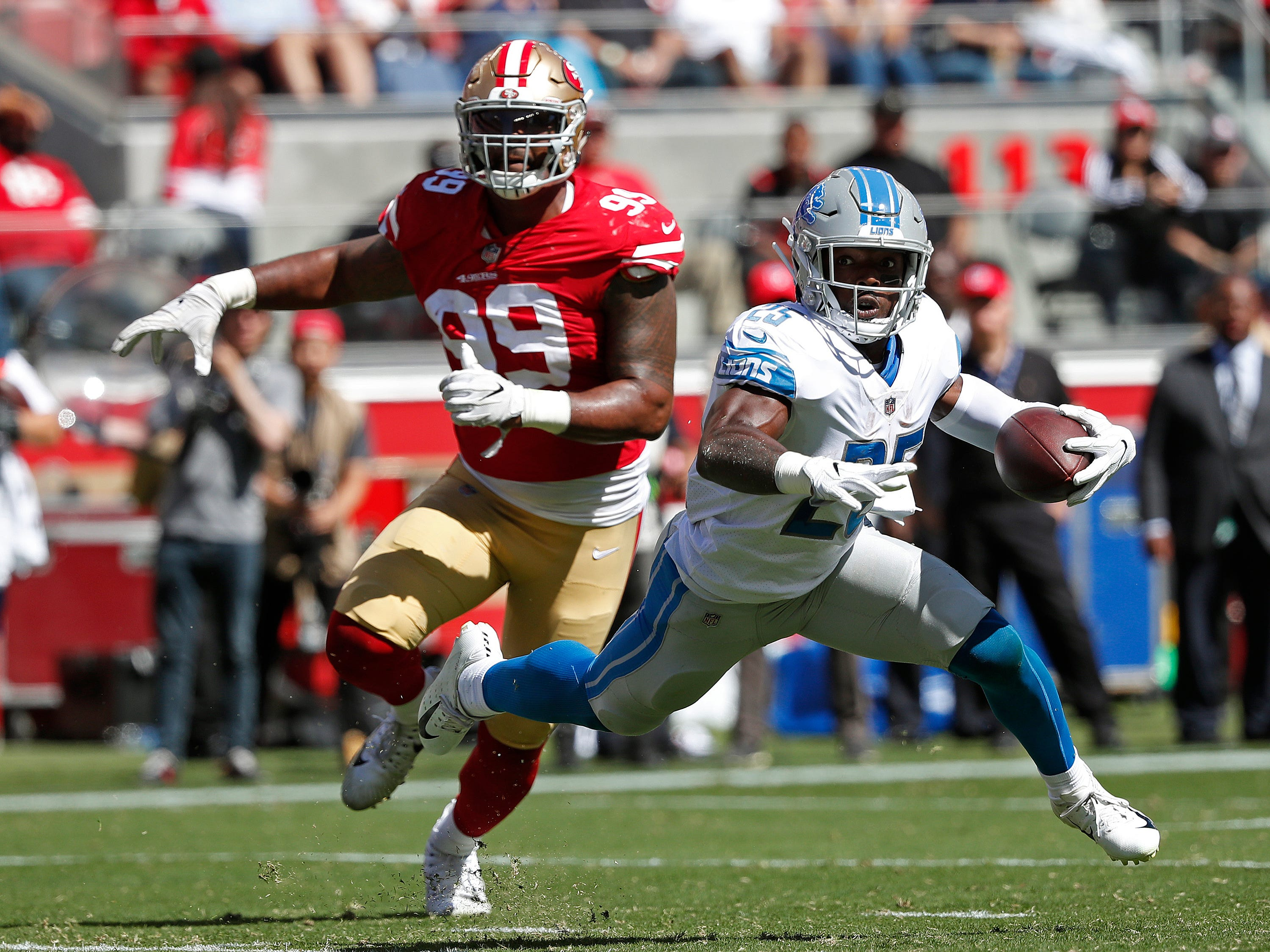 Detroit Lions running back Theo Riddick runs with the ball as San Francisco 49ers defensive end DeForest Buckner (99) pursues during the first half.
