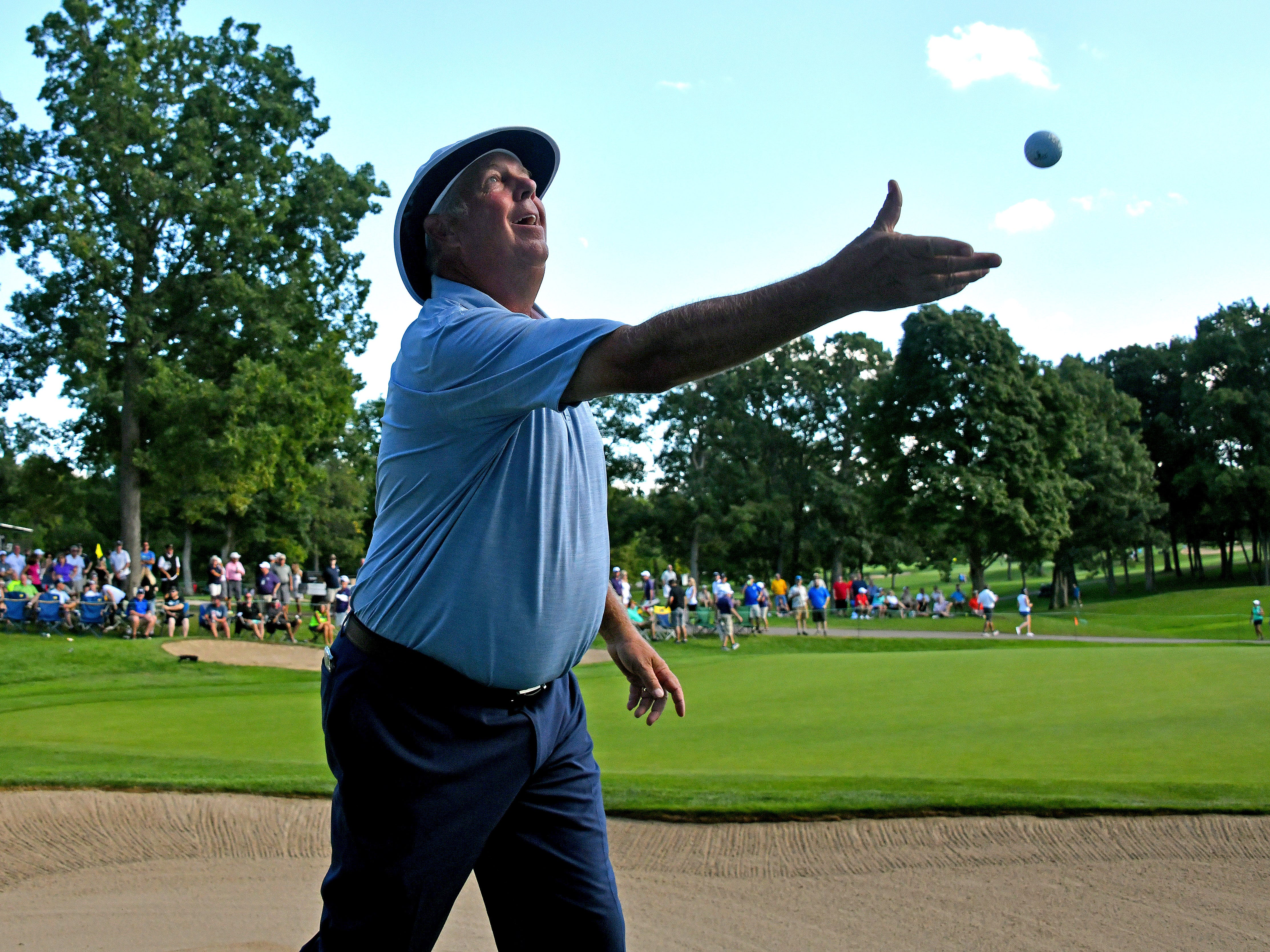 Kirk Triplett throws a souvenir ball to fans in the grandstands on the 17th green.