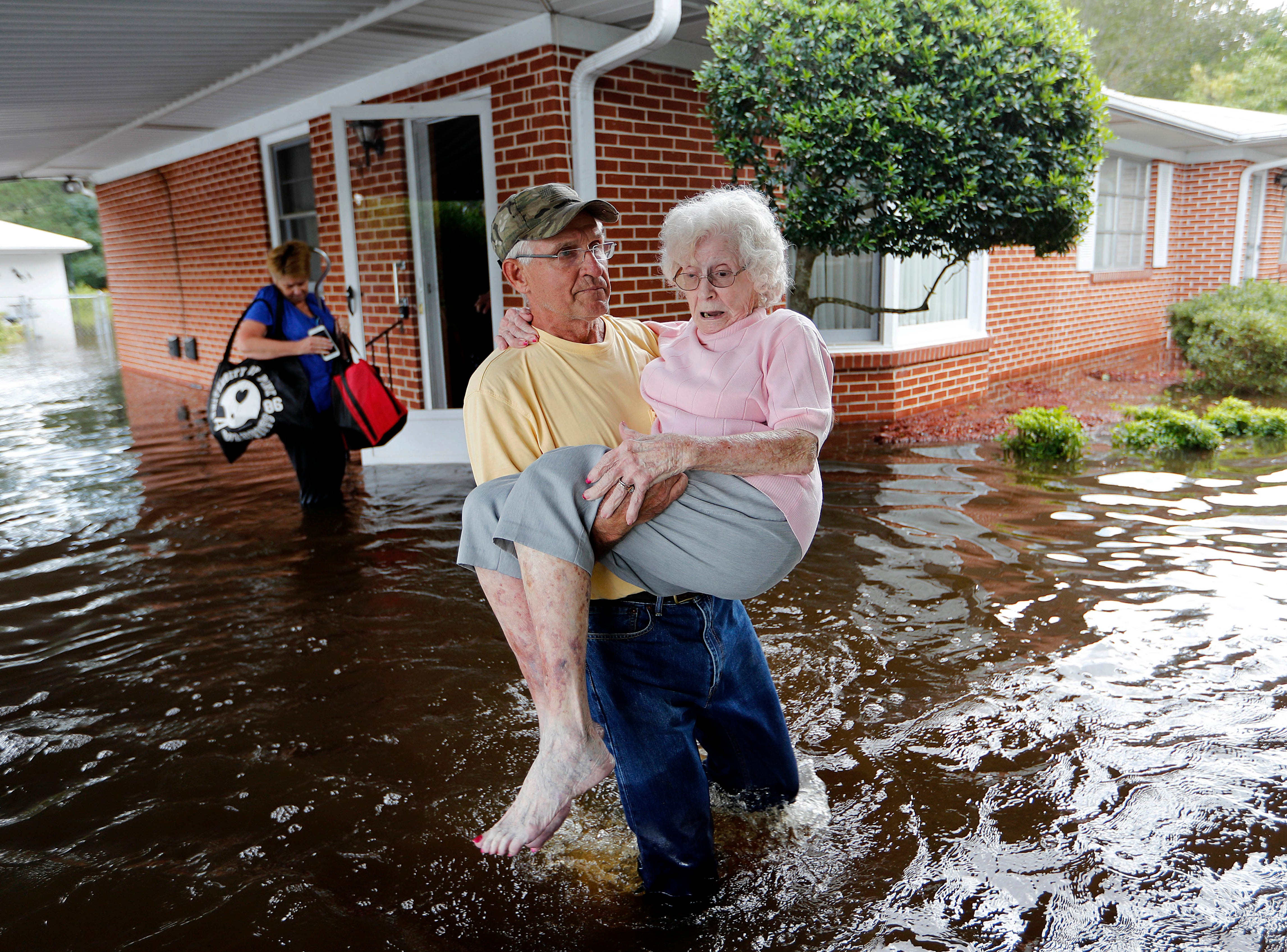 Bob Richling carries Iris Darden, 84, out of her flooded home as her daughter-in-law, Pam Darden, gathers her belongings in the aftermath of Hurricane Florence in Spring Lake, N.C.