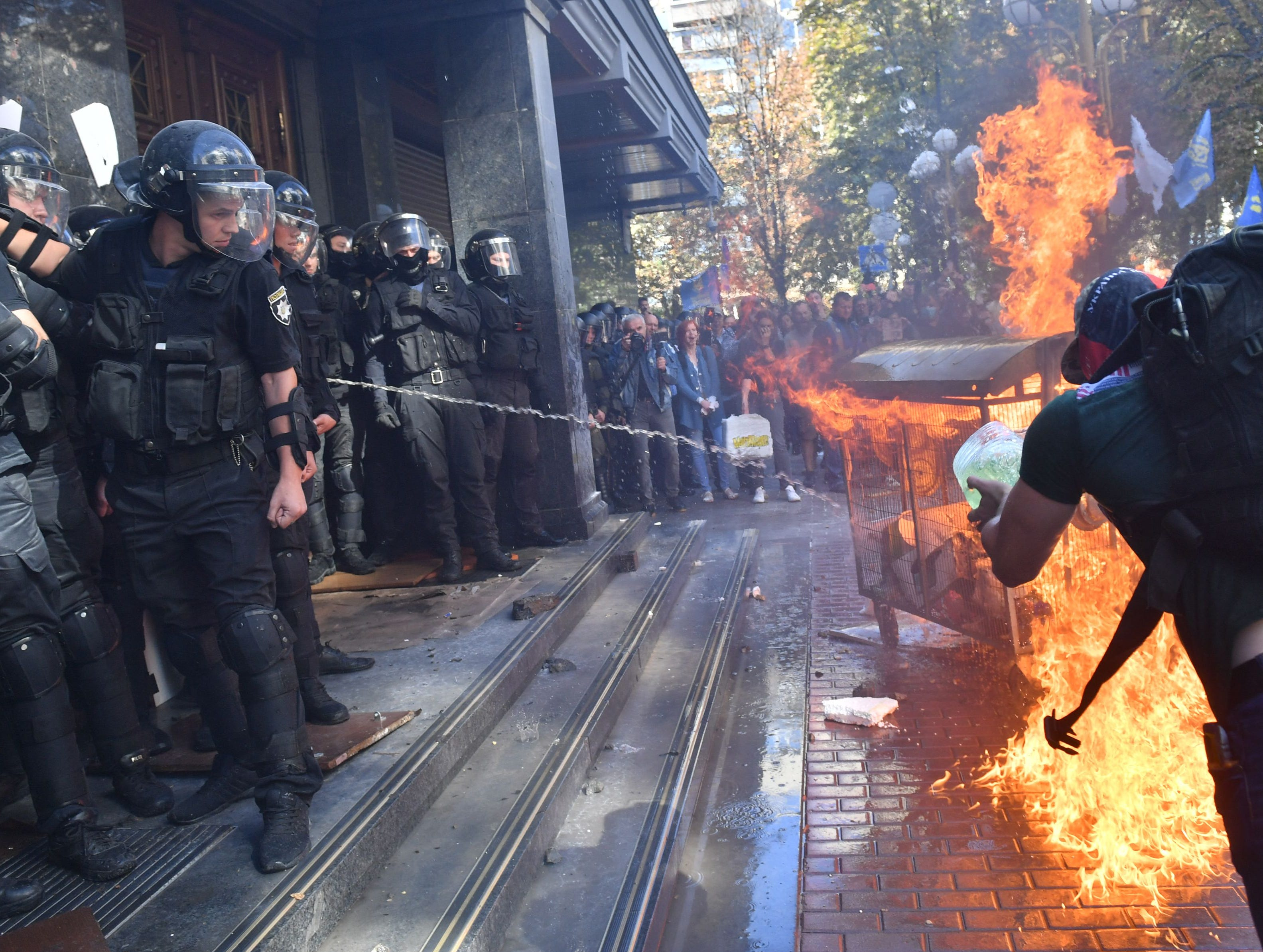 Activists of Ukrainian far-right groups burn a fire during their clashing with riot police in front of the Prosecutor General's Office in Kiev on September 17, 2018 as the Ukrainian authorities extradited a Russian citizen wanted by Moscow as a suspected Islamic State fighter.