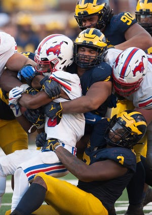Michigan's Carlo Kemp (middle) and Rashan Gary return to action Saturday against Nebraska.
