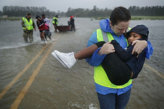JAMES CITY, NC - SEPTEMBER 14:  Volunteer Amber Hersel from the Civilian Crisis Response Team helps rescue 7-year-old Keiyana Cromartie and her family from their flooded home September 14, 2018 in James City, United States. Hurricane Florence made landfall in North Carolina as a Category 1 storm and flooding from the heavy rain is forcing hundreds of people to call for emergency rescues in the area around New Bern, North Carolina, which sits at the confluence of the Nueces and Trent rivers.  (Photo by Chip Somodevilla/Getty Images)