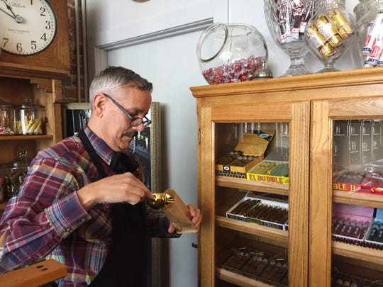 Tony Vallejos, owner of The Fort Collins Candy Store Emporium, 227 Jefferson St., fills a small bag with Atomic fireballs, a classic penny candy.