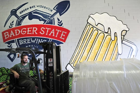 Badger State Brewing head brewer Sam Yanda moves new brewing equipment into the company's Green Bay brewery on Monday.