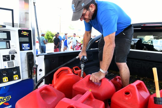 Jacques Lamarche fills gas cans as walkers lineup to will their gas cans in Wilmington following Hurricane Florence  Monday, September 17, 2018.