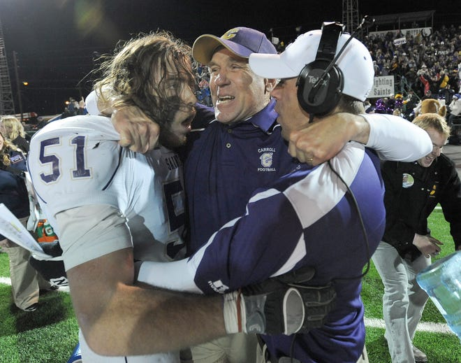 Carroll College football coach Mike Van Diest celebrates with linebacker Lynn Mallory and assistant coach Shane Van Diest, oldest son of the head coach, following the 2010 NAIA championship game in Rome, Ga. Carroll College defeated Sioux Falls 10-7.