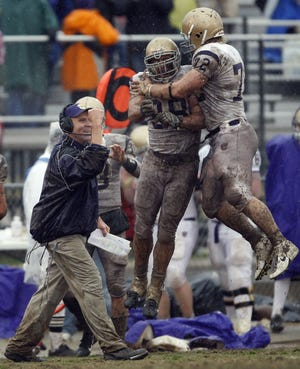 Carroll College head coach Mike Van Diest celebrates a defensive stop along with Will Hamilton (left) and Mike Paffhausen during the 2007 NAIA national championship game. Carroll defeated the University of Sioux Falls 17-9.