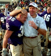 Carroll coach Mike Van Diest celebrates with linebacker Joe Horne following an NAIA playoff victory in 2000.