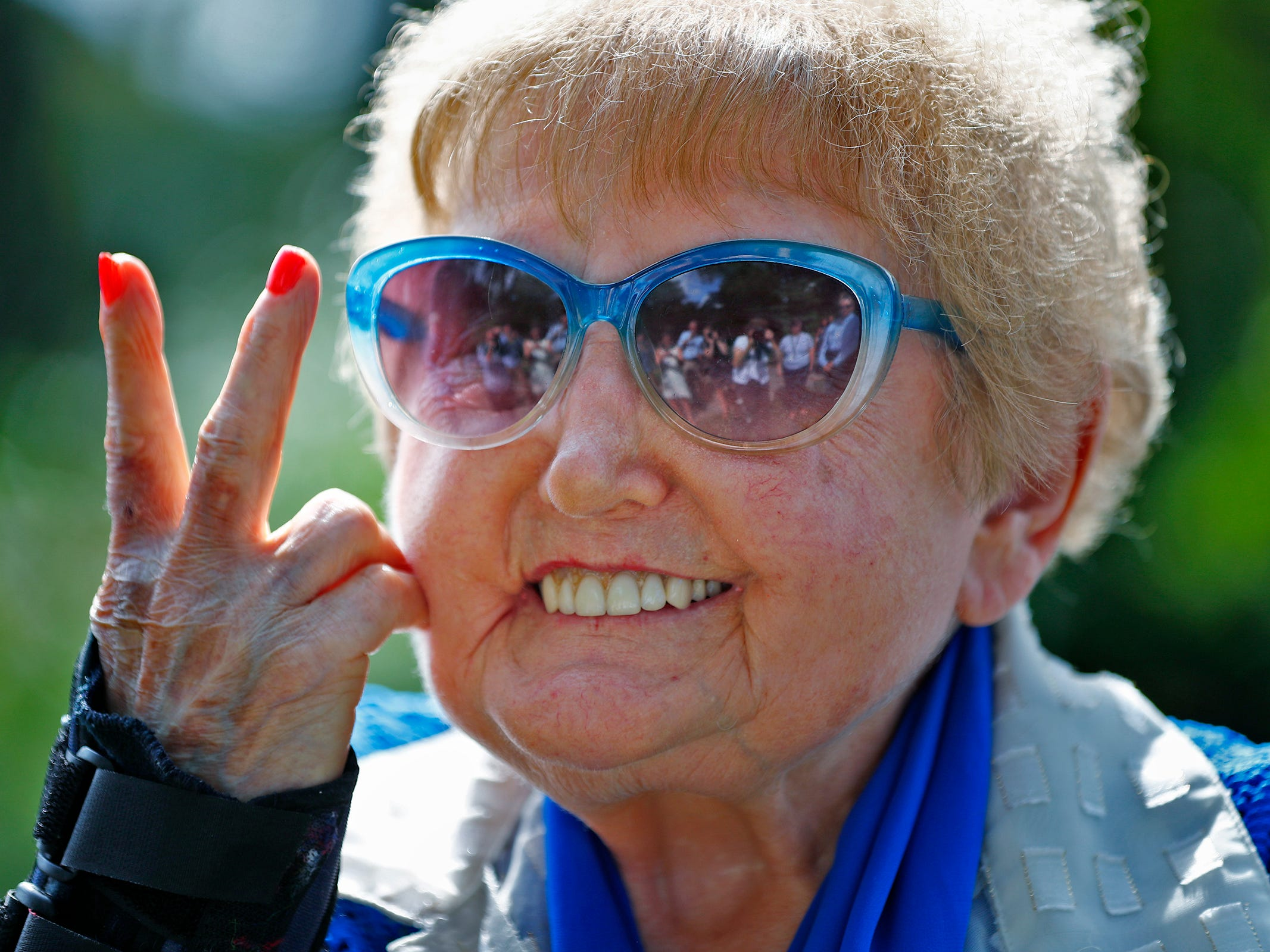 """Holocaust survivor Eva Kor gives the peace sign and smiles during the planting of the Eva Kor Peace Garden at Newfields, Monday, Sept. 17, 2018.  Students viewed the documentary """"Eva,"""" about Holocaust survivor Eva Kor, and then helped in the planting of the Peace Garden.  Kor also spoke with the students, asking them to think of one thing to make the world better."""