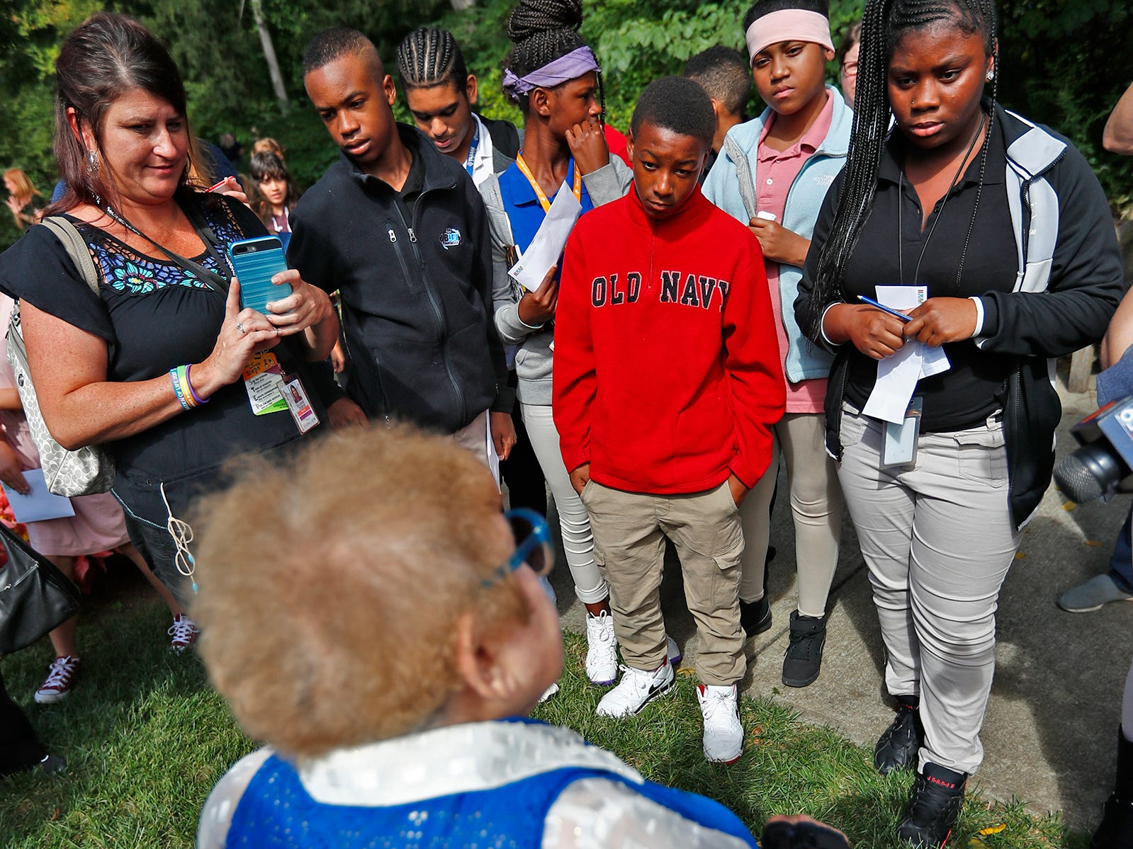 """Eva Kor, back to camera, speaks to students after they planed flower seeds at the Eva Kor Peace Garden at Newfields, Monday, Sept. 17, 2018.  Students viewed the documentary """"Eva,"""" about Holocaust survivor Eva Kor, and then helped in the planting of the Peace Garden.  Kor also spoke with the students, asking them to think of one thing to make the world better."""