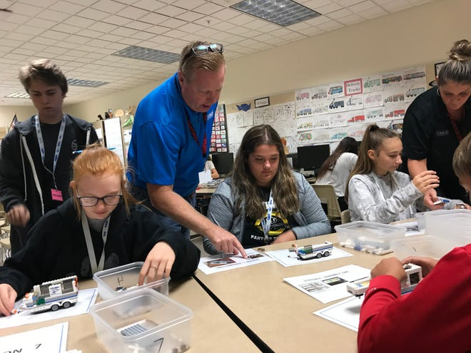 Rick Schutt of Thor Industries helps students at NorthWood Middle School put together miniature recreational vehicles on Sept. 7, 2018.