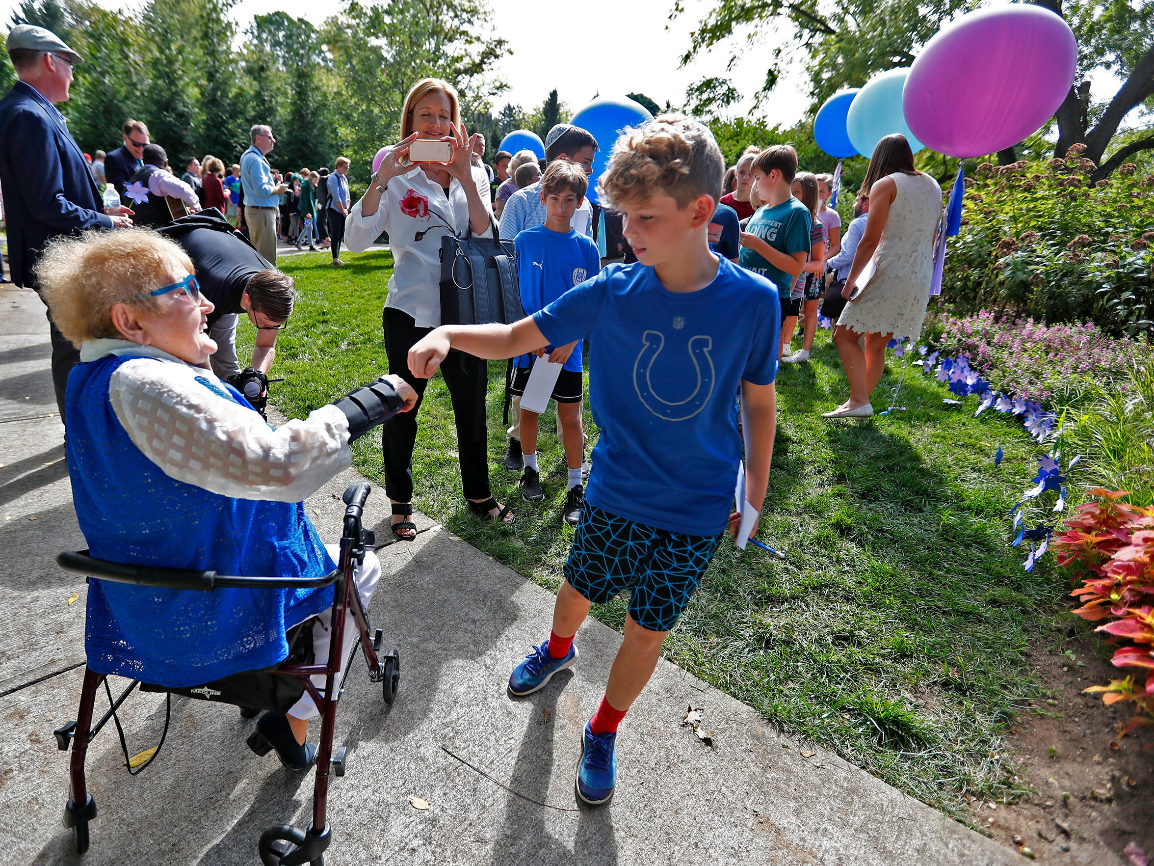 """Eva Kor, left, fist bumps with students after they planted flower seeds at the Eva Kor Peace Garden at Newfields, Monday, Sept. 17, 2018.  Students viewed the documentary """"Eva,"""" about Holocaust survivor Eva Kor, and then helped in the planting of the Peace Garden.  Kor also spoke with the students, asking them to think of one thing to make the world better."""