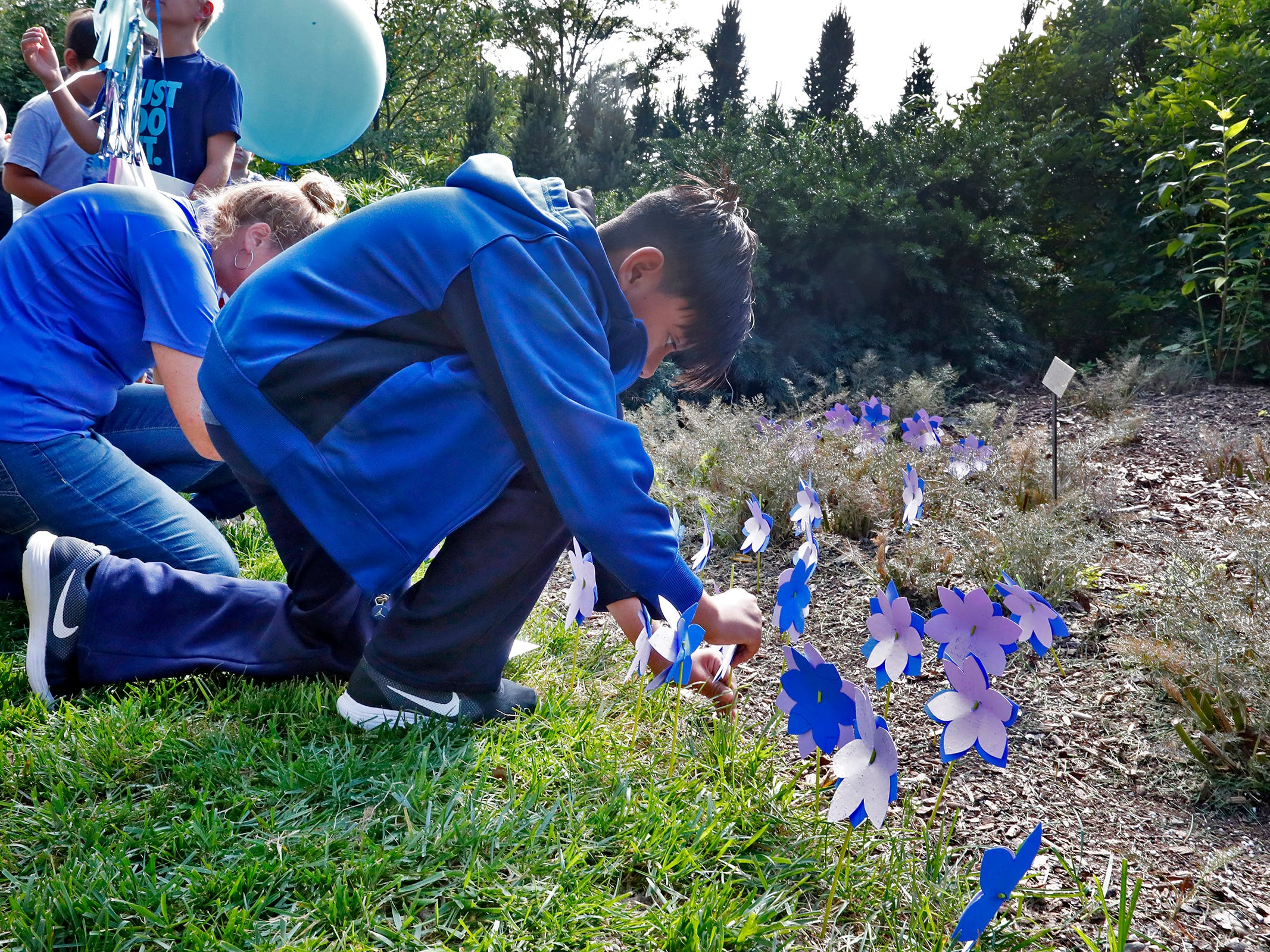 """Students plant flower seeds with paper flowers and notes during the planting of the Eva Kor Peace Garden at Newfields, Monday, Sept. 17, 2018.  Students viewed the documentary """"Eva,"""" about Holocaust survivor Eva Kor, and then helped in the planting of the Peace Garden.  Kor also spoke with the students, asking them to think of one thing to make the world better."""