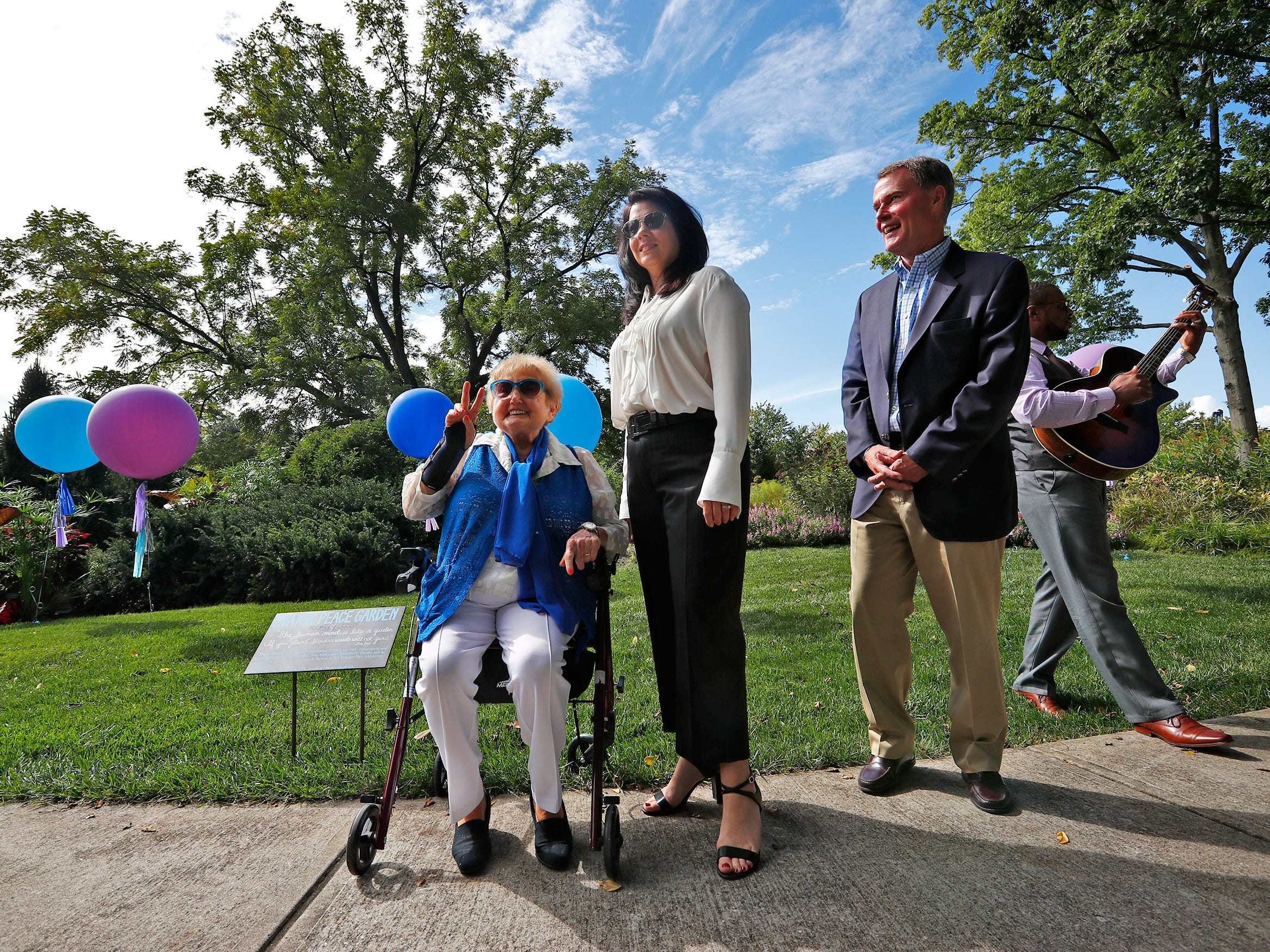 """Eva Kor, left, shows the peace sign, as she sits by First Lady Janet Holcomb, Mayor Joe Hogsett, and Tyron Cooper, at the Eva Kor Peace Garden at Newfields, Monday, Sept. 17, 2018.  Students viewed the documentary """"Eva,"""" about  Holocaust survivor Eva Kor, and then helped in the planting of the Peace Garden.  Kor also spoke with the students, asking them to think of one thing to make the world better."""