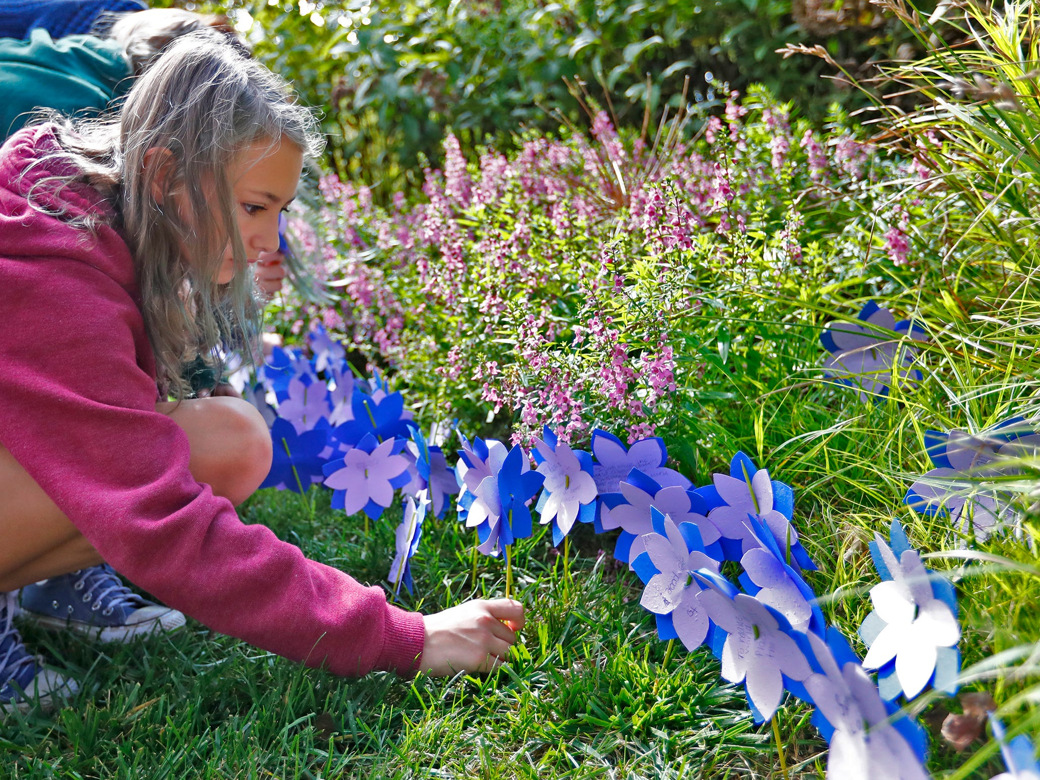 """Chloe Sequoy, from Bloomington Project School, plants flower seeds with a paper flower and note during the planting of the Eva Kor Peace Garden at Newfields, Monday, Sept. 17, 2018.  Students viewed the documentary """"Eva,"""" about Holocaust survivor Eva Kor, and then helped in the planting of the Peace Garden.  Kor also spoke with the students, asking them to think of one thing to make the world better."""