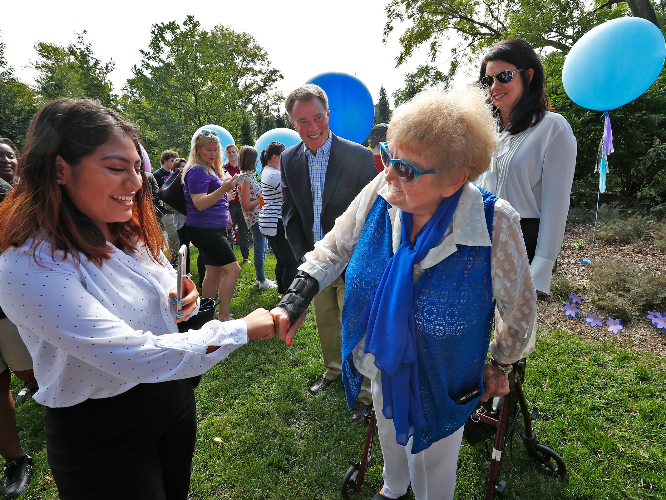 """Eva Kor, right, fist bumps with students after they planted flower seeds at the Eva Kor Peace Garden at Newfields, Monday, Sept. 17, 2018.  Students viewed the documentary """"Eva,"""" about Holocaust survivor Eva Kor, and then helped in the planting of the Peace Garden.  Kor also spoke with the students, asking them to think of one thing to make the world better."""