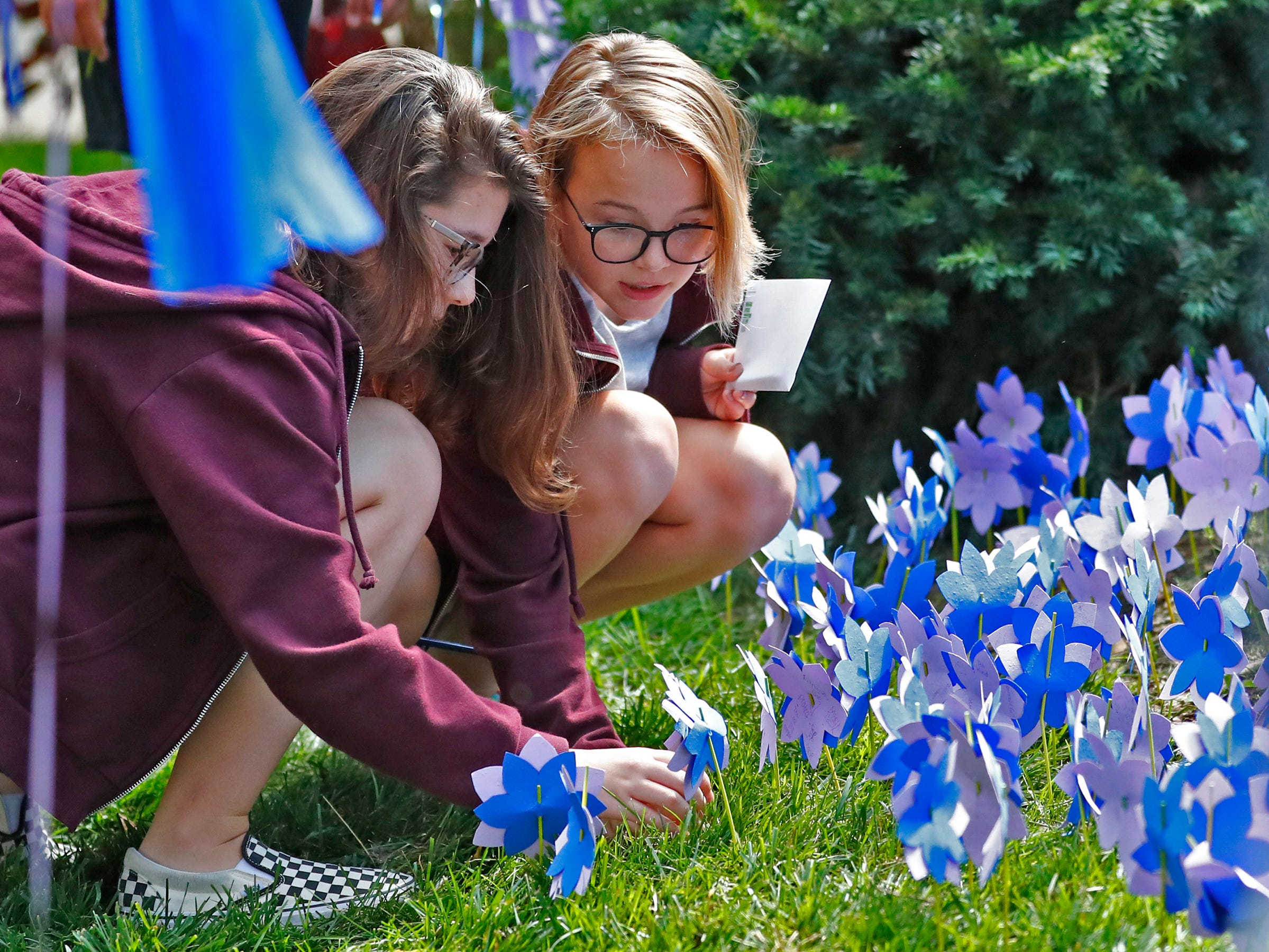 """Victoria Crouch, left, and Keller Wason, with Bloomington Project School, and other students plant flower seeds with paper flowers and notes during the planting of the Eva Kor Peace Garden at Newfields, Monday, Sept. 17, 2018.  Students viewed the documentary """"Eva,"""" about Holocaust survivor Eva Kor, and then helped in the planting of the Peace Garden.  Kor also spoke with the students, asking them to think of one thing to make the world better."""