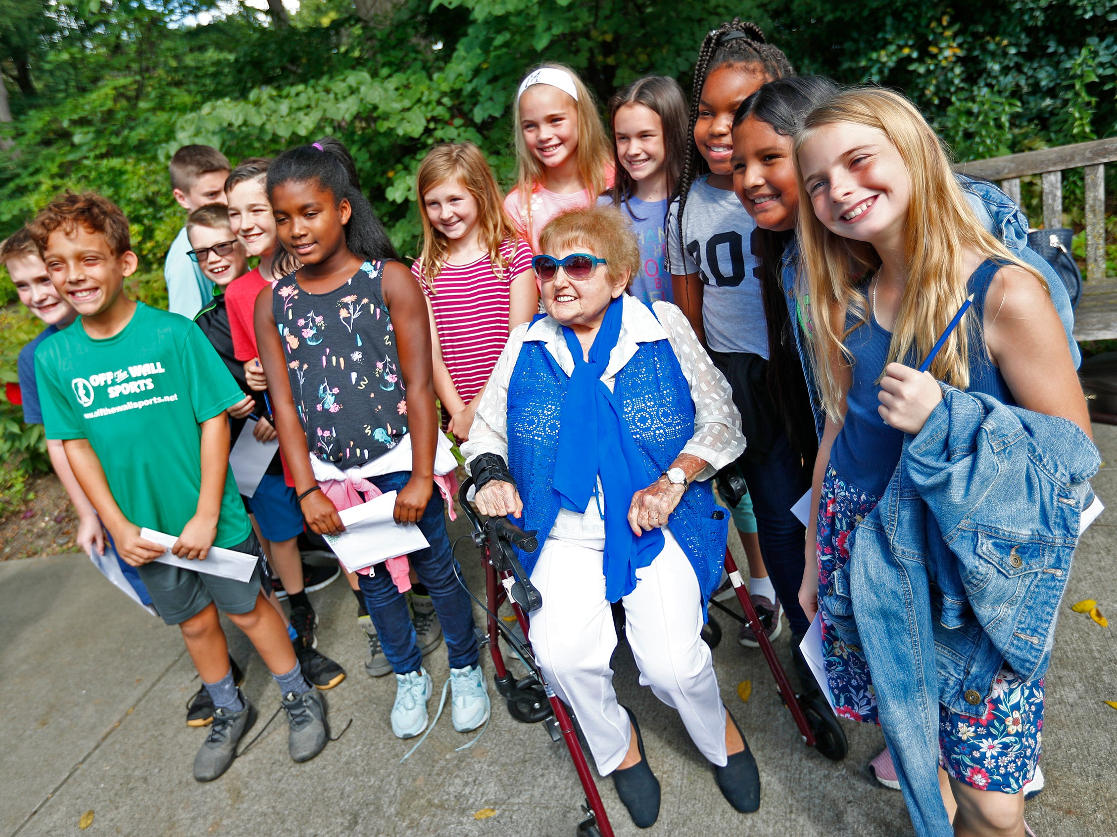 """Holocaust survivor Eva Kor, center, poses for photos with students from Allisonville Elementary School, during the planting of the Eva Kor Peace Garden at Newfields, Monday, Sept. 17, 2018.  Students viewed the documentary """"Eva,"""" about Kor, and then helped in the planting of the Peace Garden.  Kor also spoke with the students, asking them to think of one thing to make the world better."""