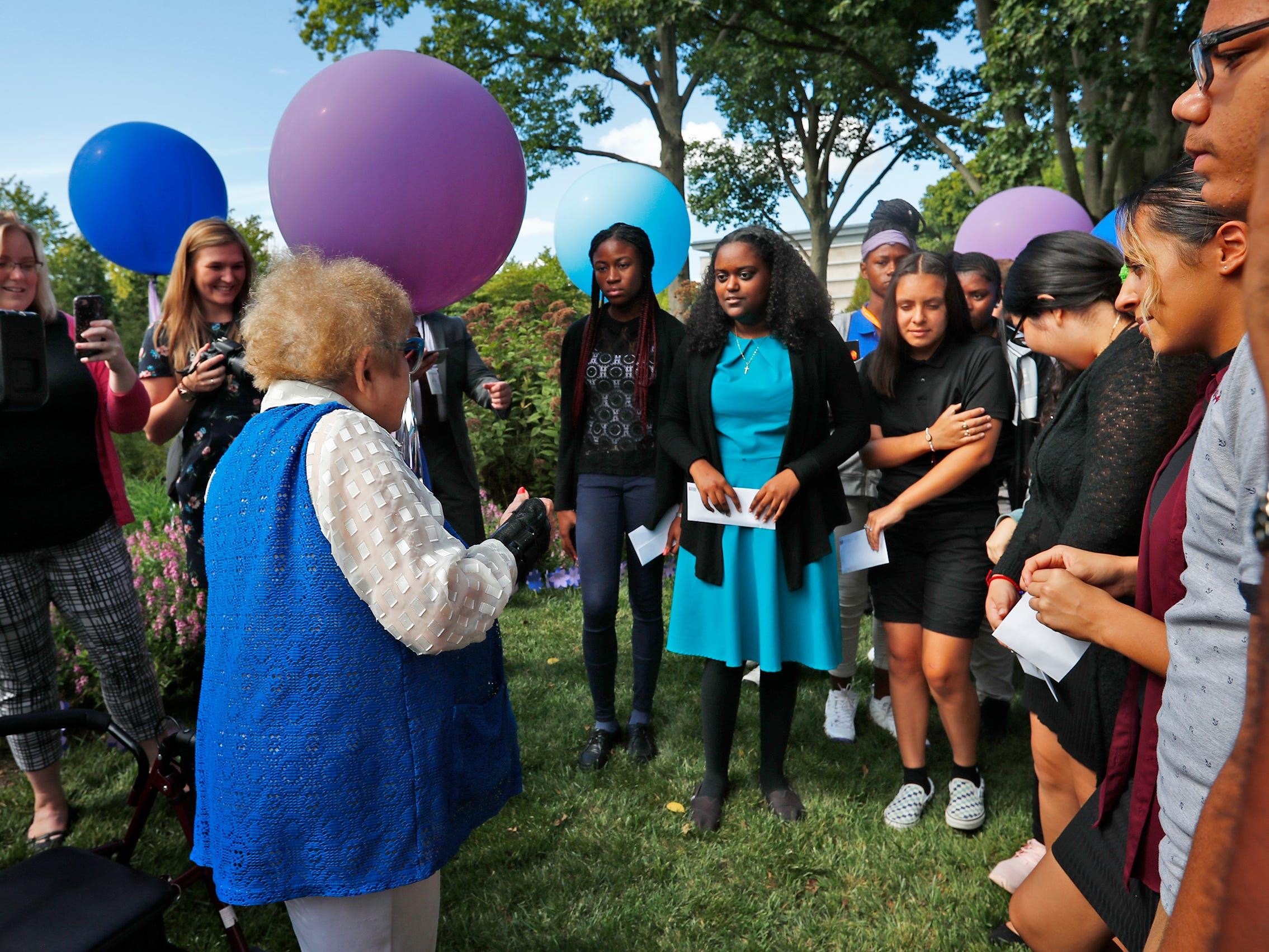"""Eva Kor, left, speaks to students after they planed flower seeds at the Eva Kor Peace Garden at Newfields, Monday, Sept. 17, 2018.  Students viewed the documentary """"Eva,"""" about Holocaust survivor Eva Kor, and then helped in the planting of the Peace Garden.  Kor also spoke with the students, asking them to think of one thing to make the world better."""