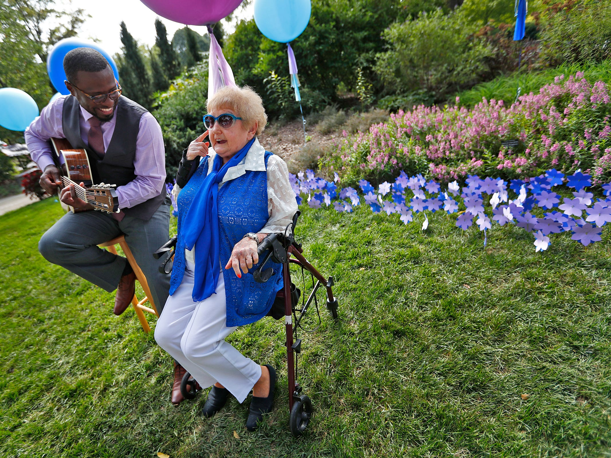 """Holocaust survivor Eva Kor, right, talks with guitarist Tyron Cooper at the Eva Kor Peace Garden at Newfields, Monday, Sept. 17, 2018.  Students viewed the documentary """"Eva,"""" about Kor, and then helped in the planting of the Peace Garden.  Kor also spoke with the students, asking them to think of one thing to make the world better."""