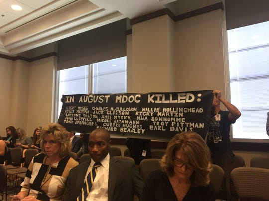 "Unidentified protesters hold a sign during the Monday, Sept. 17, 2018, legislative budget hearings for the Mississippi Department of Corrections. When the hearings began, the protesters started changing, ""Fund your sword of justice,"" and, ""MDOC kills."" They were escorted from the legislative chamber without incident."