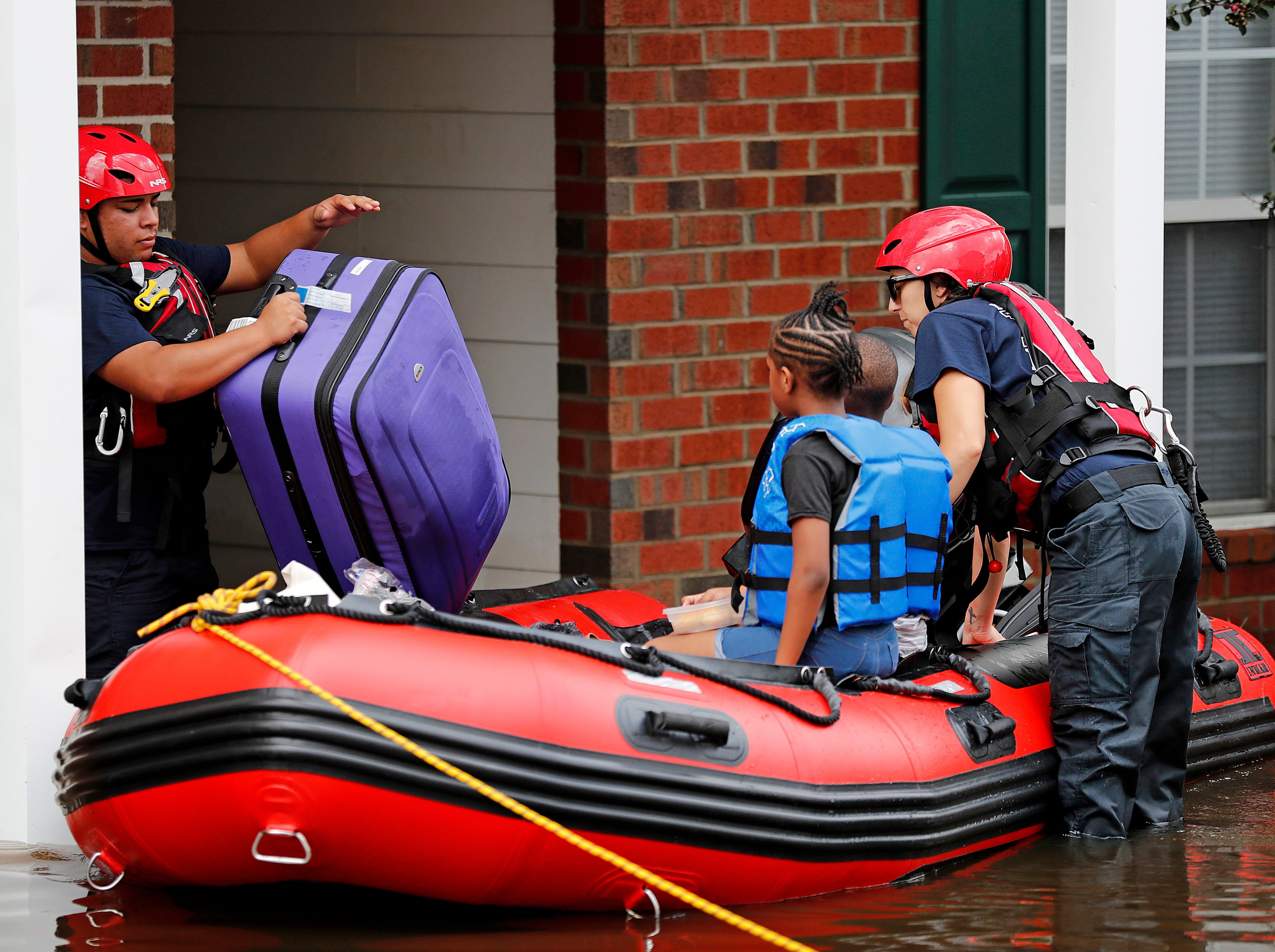 Rescue personnel evacuate residents as flooding continues in the aftermath of Hurricane Florence in Spring Lake, N.C., Monday, Sept. 17, 2018.